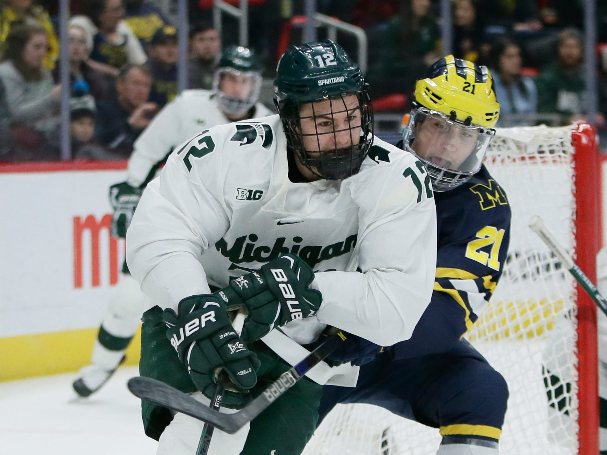 Michigan State defenseman Tommy Miller is pursued by Michigan forward Michael Pastujov during the first period on Saturday, Feb. 9, 2019, at Little Caesars Arena.