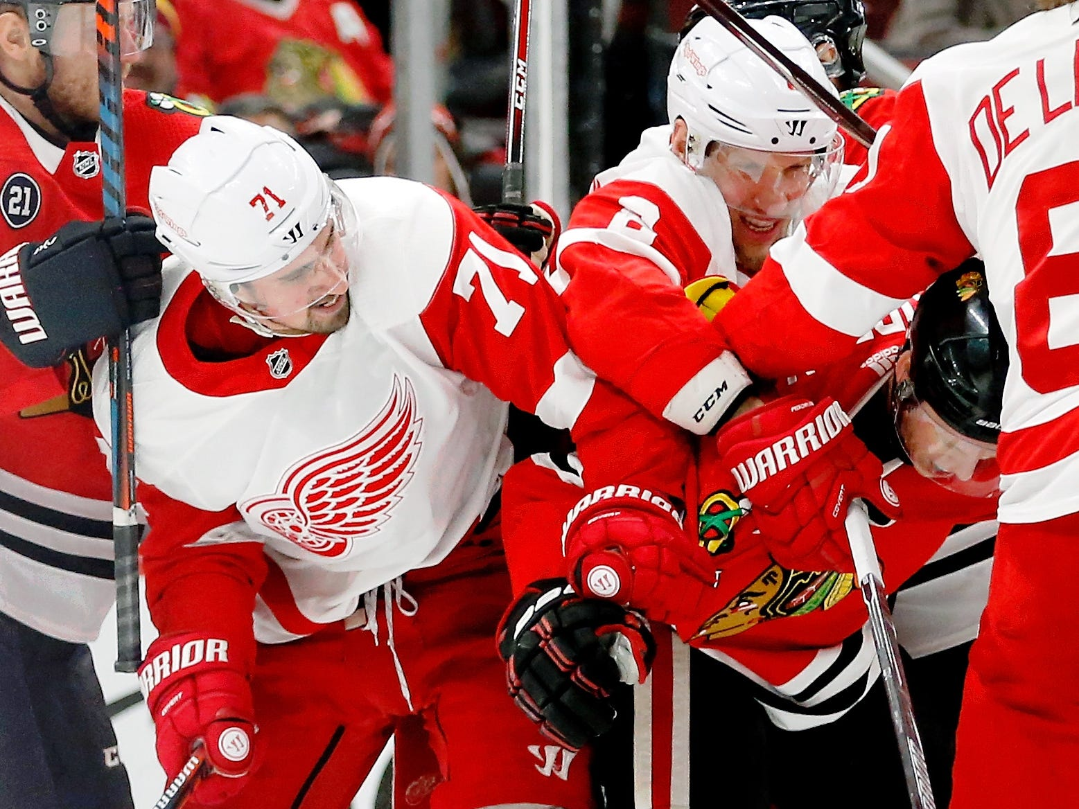 Detroit Red Wings center Dylan Larkin, left, and left wing Justin Abdelkader get in a scuffle with Chicago Blackhawks defenseman Connor Murphy during the second period at United Center on Sunday, Feb. 10, 2019.