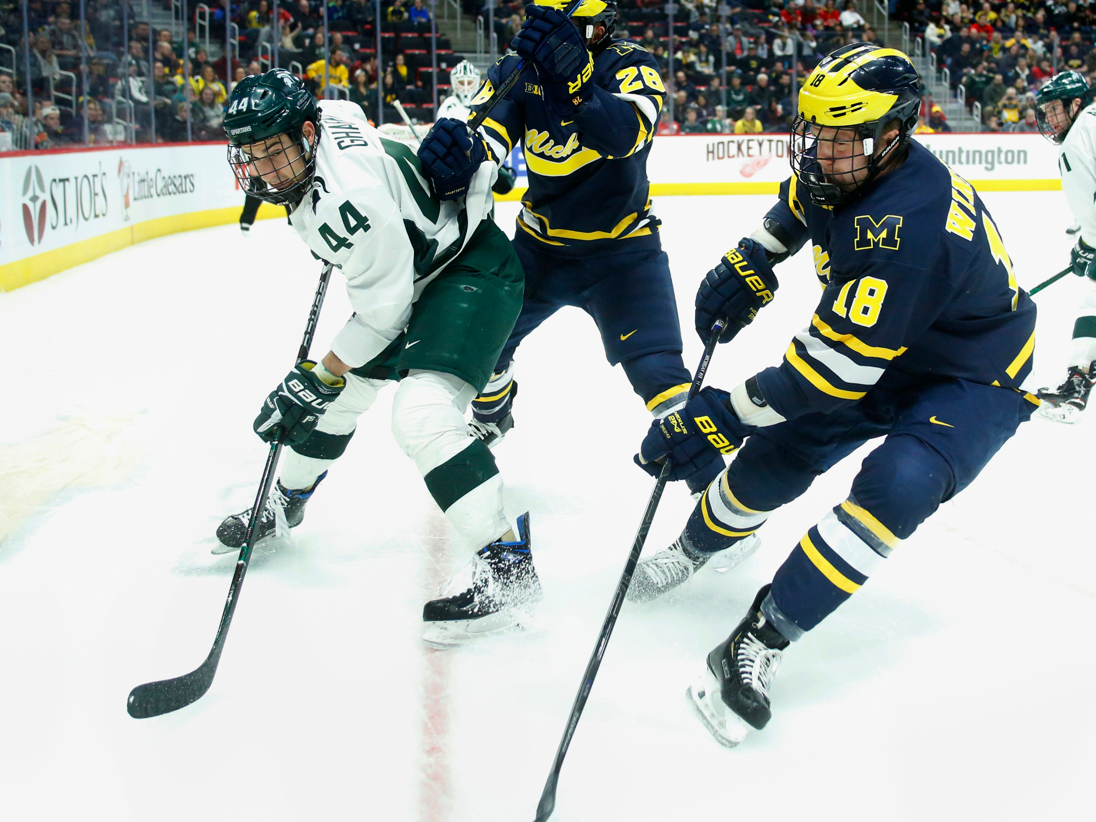 Michigan State defenseman Butrus Ghafari loses the puck to Michigan forward Adam Winborg, right, while being defended by Michigan forward Jack Randl during the first period on Saturday, Feb. 9, 2019, at Little Caesars Arena.