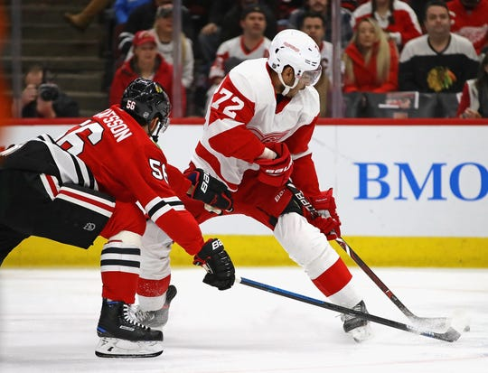 Andreas Athanasiou tries to shoot under pressure from the Blackhawks' Erik Gustafsson on Sunday in Chicago.