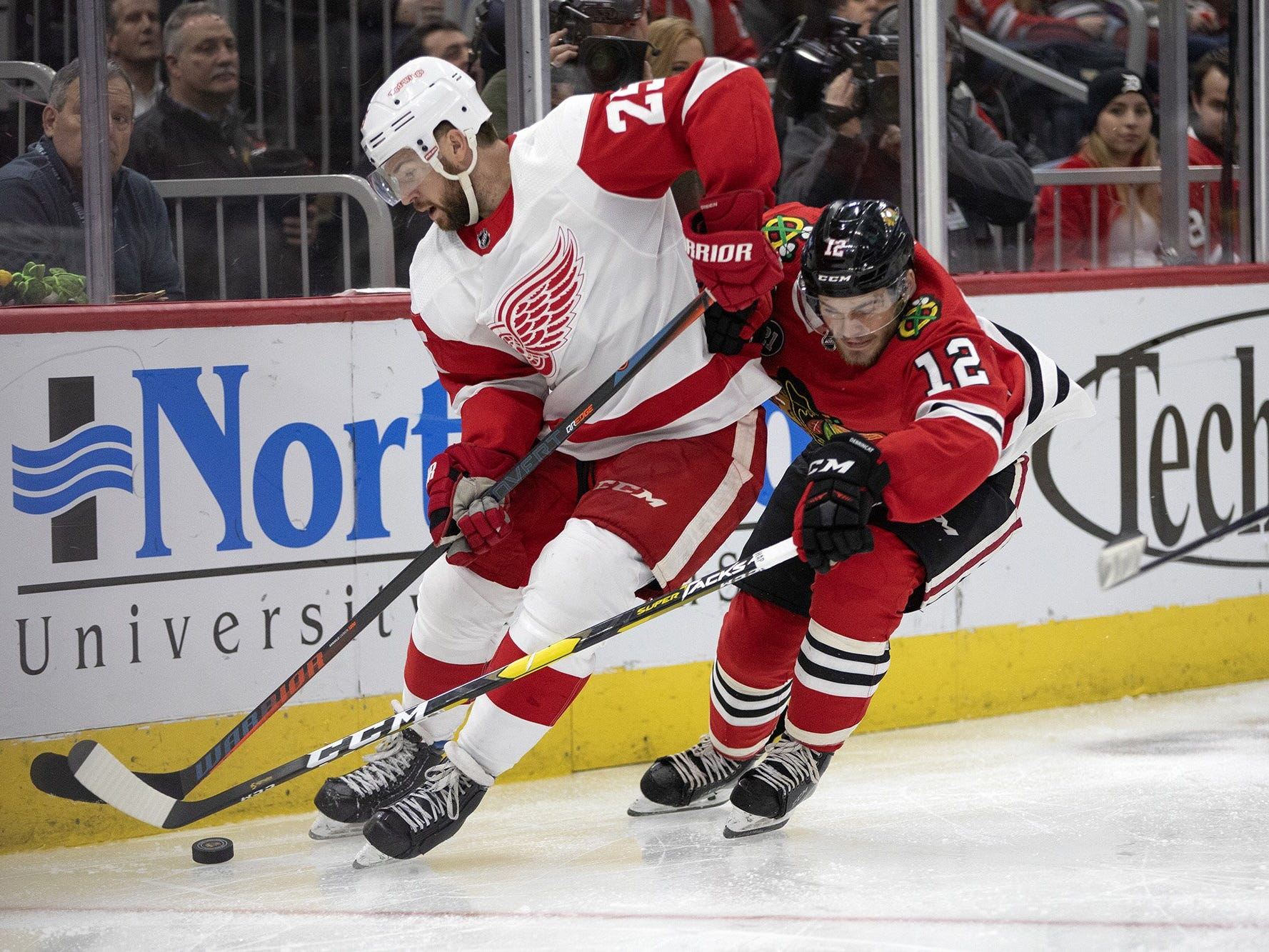 Chicago Blackhawks left wing Alex DeBrincat and Detroit Red Wings defenseman Mike Green fight for control of the puck during the third period on Sunday, Feb. 10, 2019, at the United Center in Chicago.
