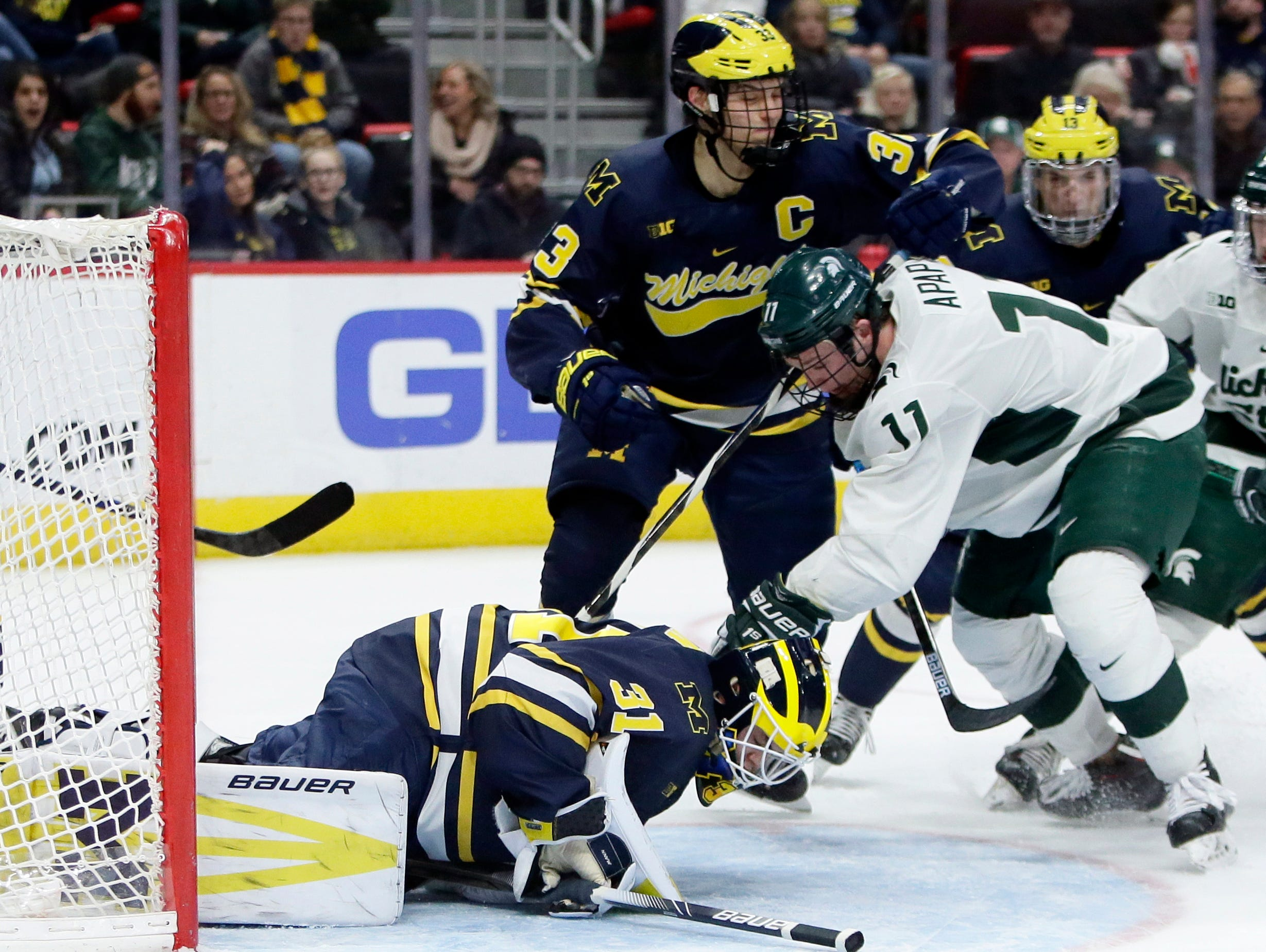 Michigan goaltender Strauss Mann covers the puck on a shot by Michigan State forward Tommy Apap with Michigan defenseman Joseph Cecconi helping defend the goal during the second period on Saturday, Feb. 9, 2019, at Little Caesars Arena.