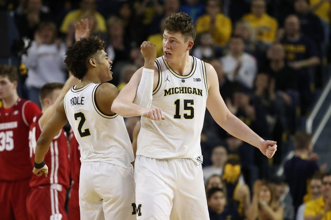 ANN ARBOR, MICHIGAN - FEBRUARY 09:  Jon Teske #15 of the Michigan Wolverines celebrates a second half basket with Jordan Poole #2 while playing the Wisconsin Badgers at Crisler Arena on February 09, 2019 in Ann Arbor, Michigan. Michigan won the game 61-52. (Photo by Gregory Shamus/Getty Images)