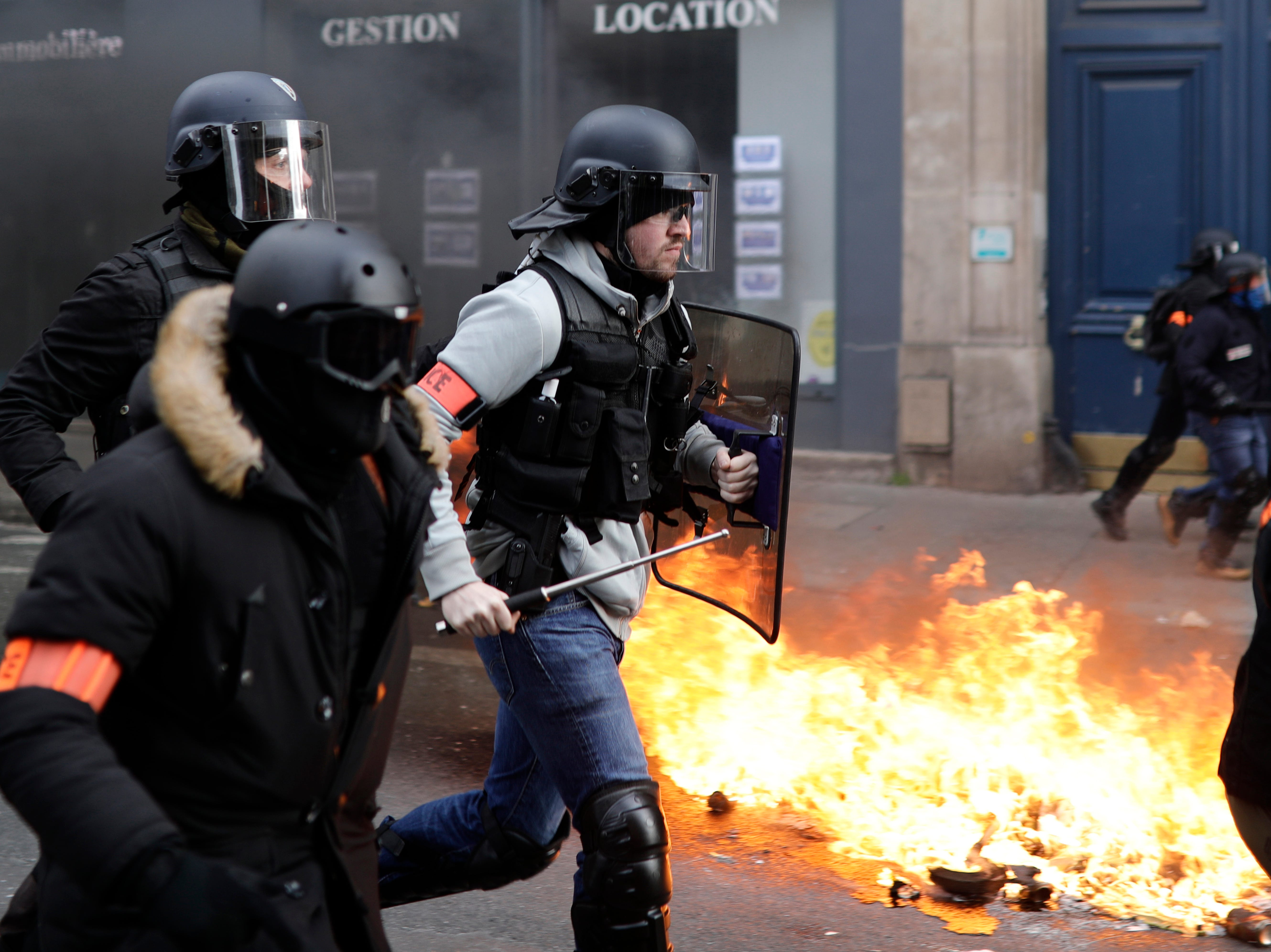 Riot police run past burning dustbins set on fire by yellow vest protesters as they keep pressure on French President Emmanuel Macron's government, for the 13th straight weekend of demonstrations, in Paris, France, Saturday, Feb. 9, 2019.