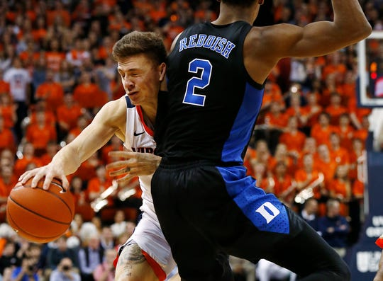 Virginia's Kyle Guy is fouled by Duke's Cam Reddish (2) during the second half.