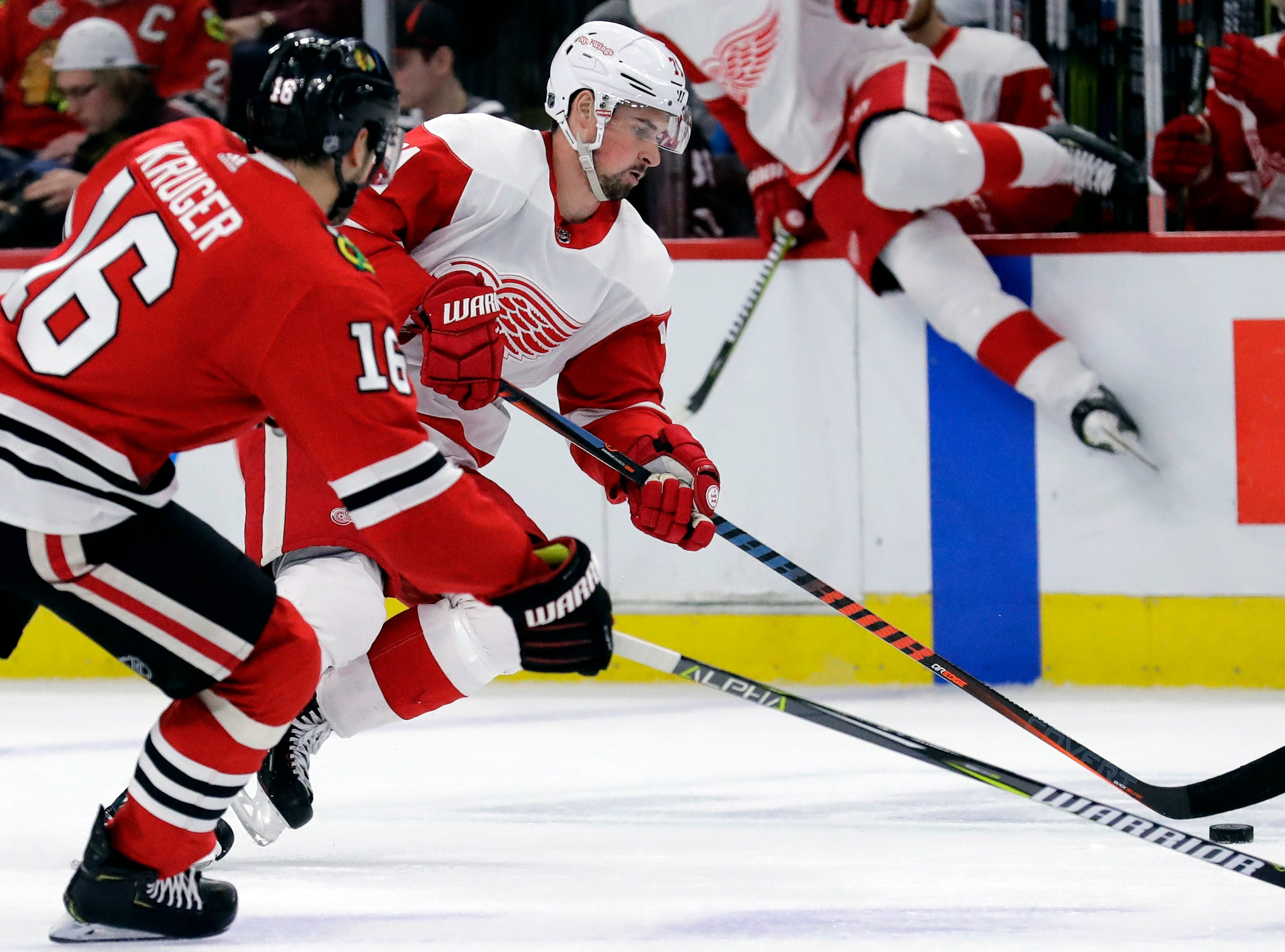 Detroit Red Wings center Dylan Larkin, front right, controls the puck against Chicago Blackhawks center Marcus Kruger, left, during the first period.