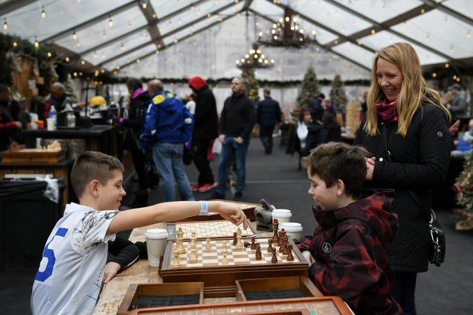 Stacey Zaborny of West Bloomfield watches while her sons, Tyler Zaborny, 10, right, and Conor Zaborny, 12, play chess in the Cadillac Lodge at the first weekend of the Quicken Loans Winter Blast in Detroit on Feb. 10, 2019.    This year the Winter Blast will take place over four consecutive weekends.
