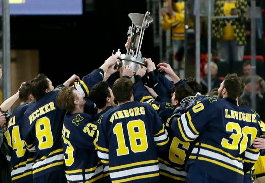 Michigan players lift the Iron D trophy after defeating Michigan State 5-2.