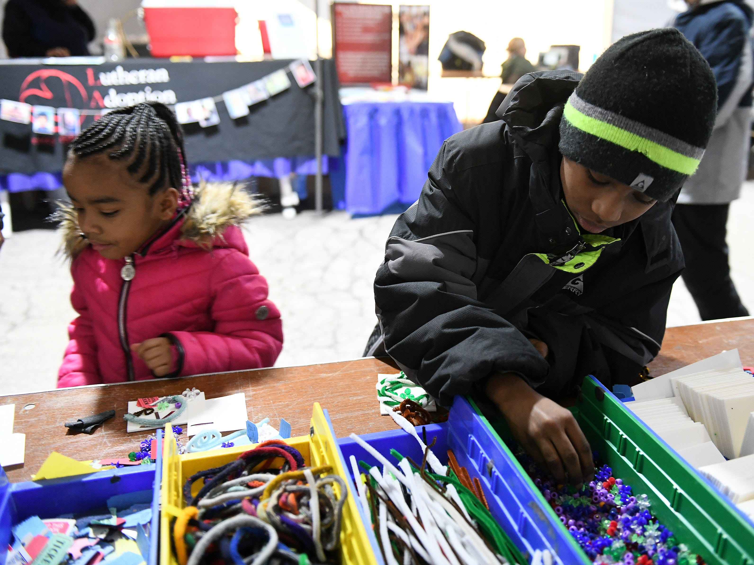 Ardise Williams, 9, right, and his sister, Tae'on Clay, 5, both of Detroit make art projects at the Arts and Scraps table in the Bedrock Comfort Zone.