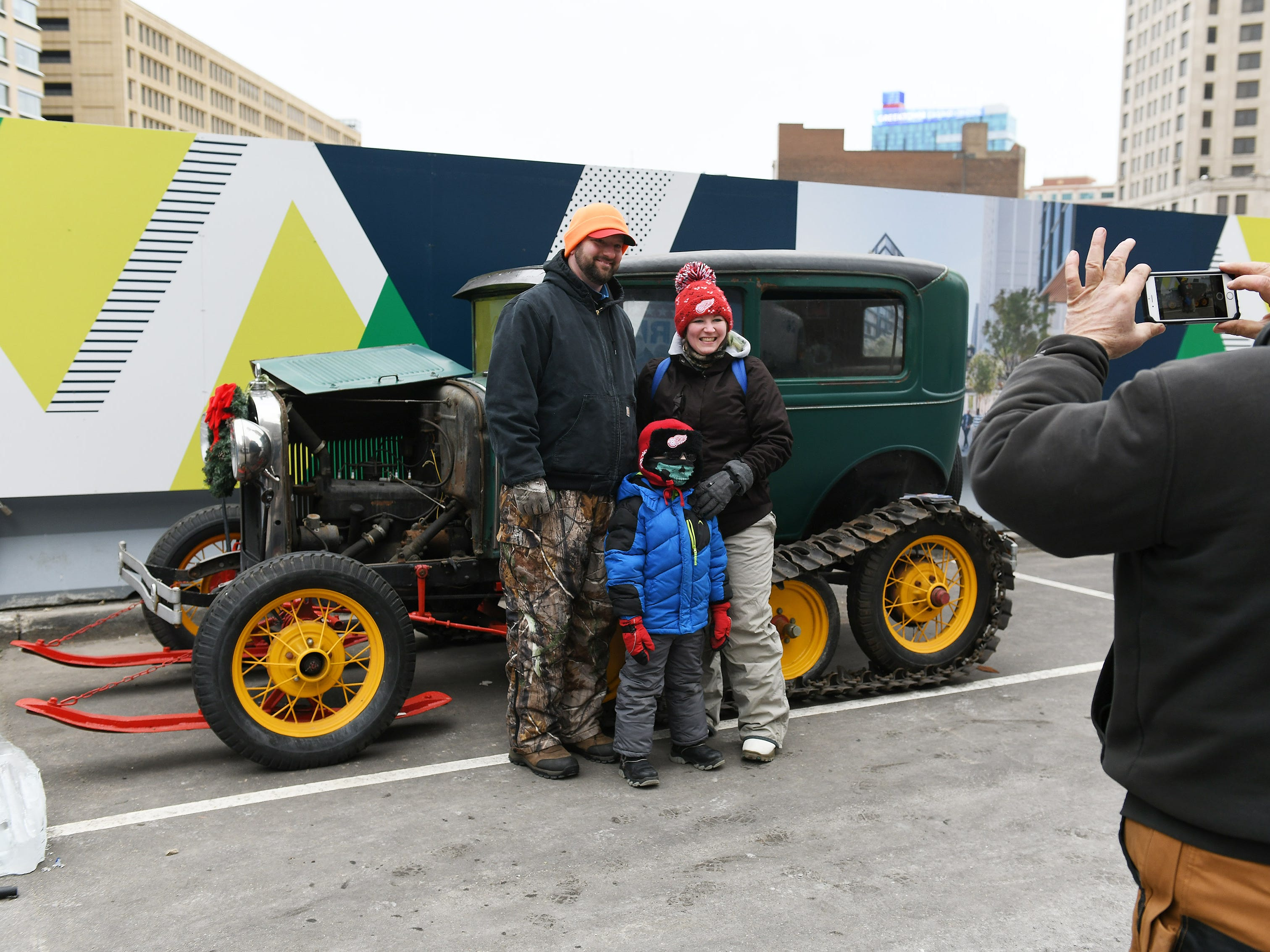 Ford Piquette Avenue Plant volunteer Randy Shelton of Dearborn takes a photo of, from left, Chris Catarino, 41, Mary Catarino, 34, and their son, Lucas, 4, with the 1930 Model A Super Snowbird conversion.