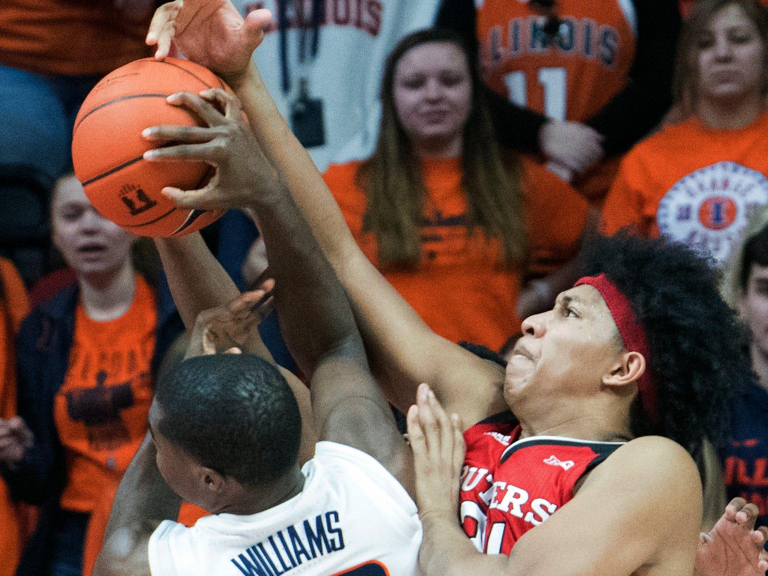 Illinois guard Da'Monte Williams (20) and Rutgers forward Ron Harper Jr. , right, struggle in the second half of an NCAA college basketball game in Champaign, Ill., Saturday, Feb. 9, 2019. (AP Photo/Robin Scholz)
