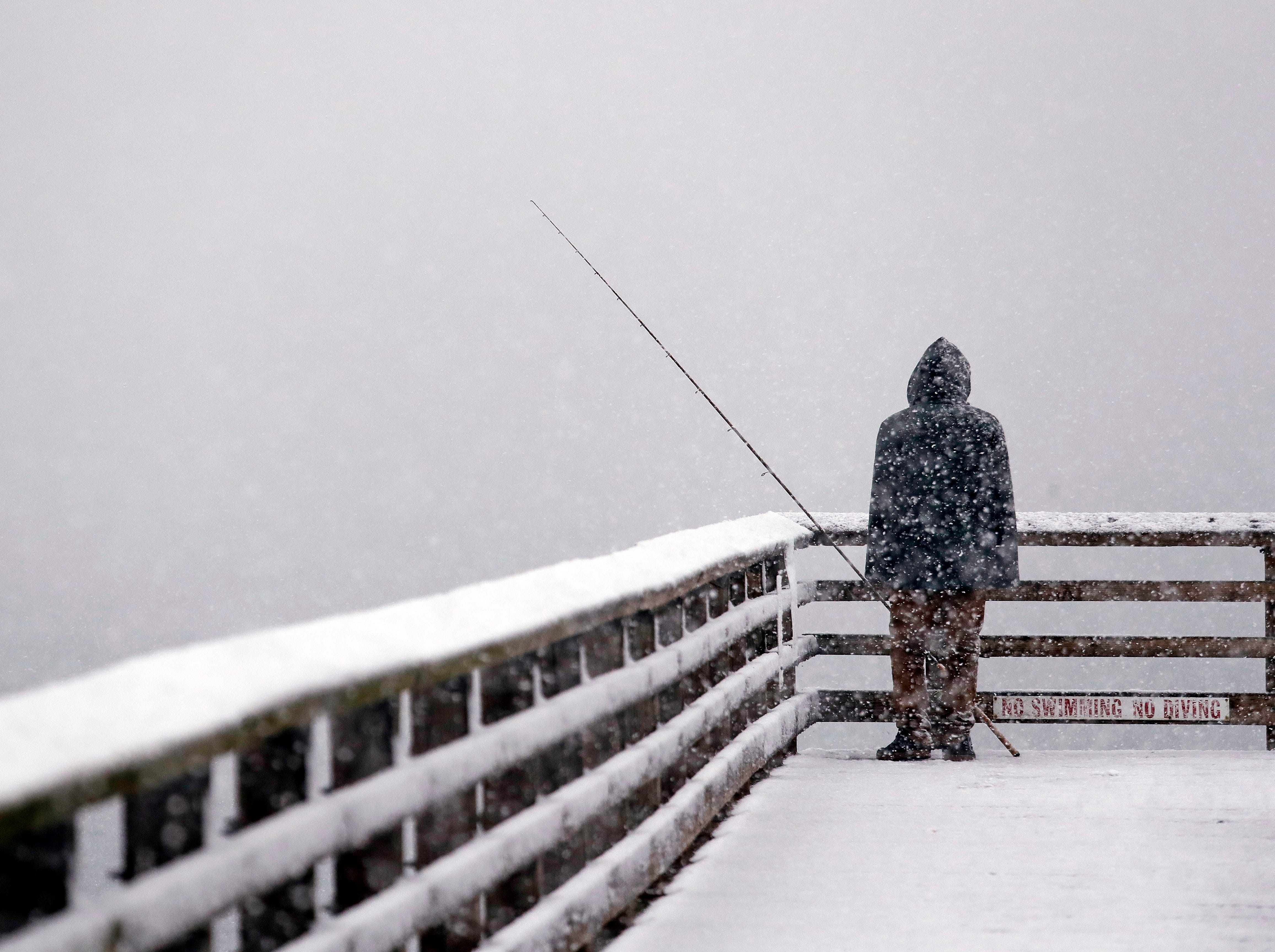 Hershel Odle looks out toward the cityscape lost in a whiteout as he fishes from a pier during a snowstorm Friday, Feb. 8, 2019, in Seattle. Officials have issued a winter storm warning for the Puget Sound region including Seattle. The National Weather Service said the warning will be in effect from noon Friday to noon Saturday, with snow accumulations of 4 to 6 inches expected in the interior lowland areas.