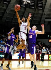 SIU guard Aaron Cook flies to the basket after sliding past Evansville forward Evan Kuhlman in the Salukis' 78-73 win Saturday.