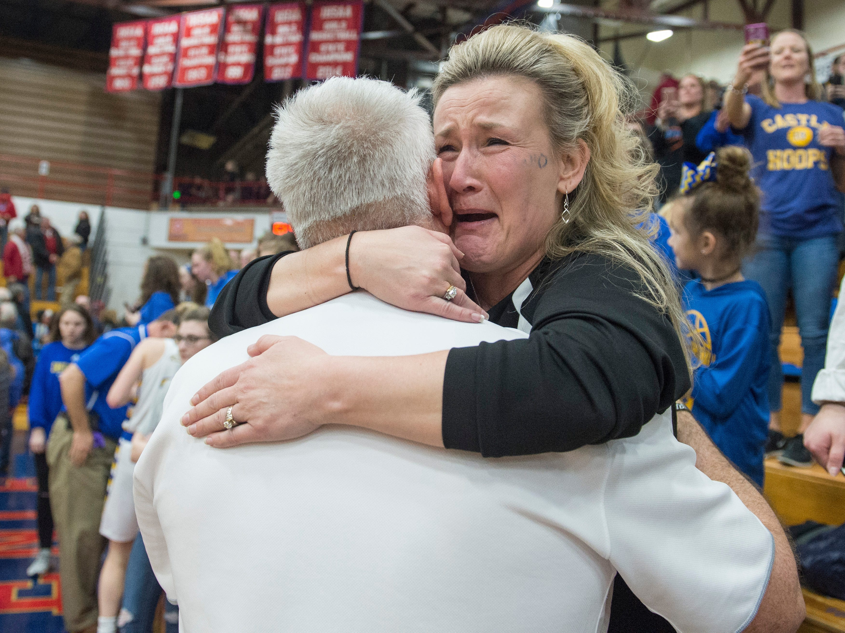 Castle Head Coach Robert Meier's wife Scarlett gives Meier a hug as tears run down her face as the Knights celebrate theirIHSAA Girls Basketball Class 4A Regional Championship game win over the Bedford North Lawrence Lady Stars at the Stars Field House in Bedford, Ind. Saturday, Feb. 9, 2019.