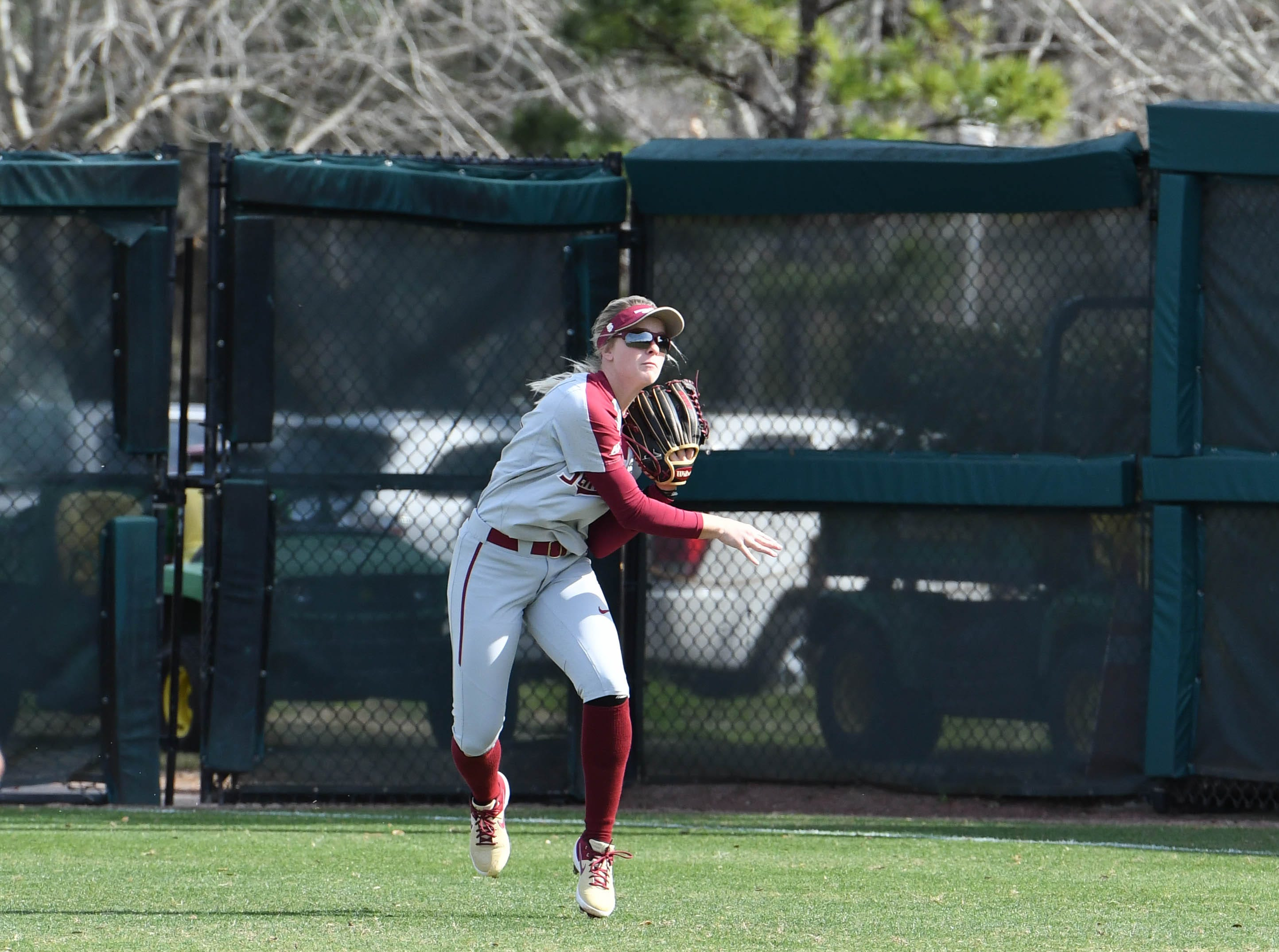 FSU freshman outfielder Makinzy Herzog (21) throwing the ball into the infield in the second inning of FSU's game against UNCG at Joanne Graf field on February 9, 2019.