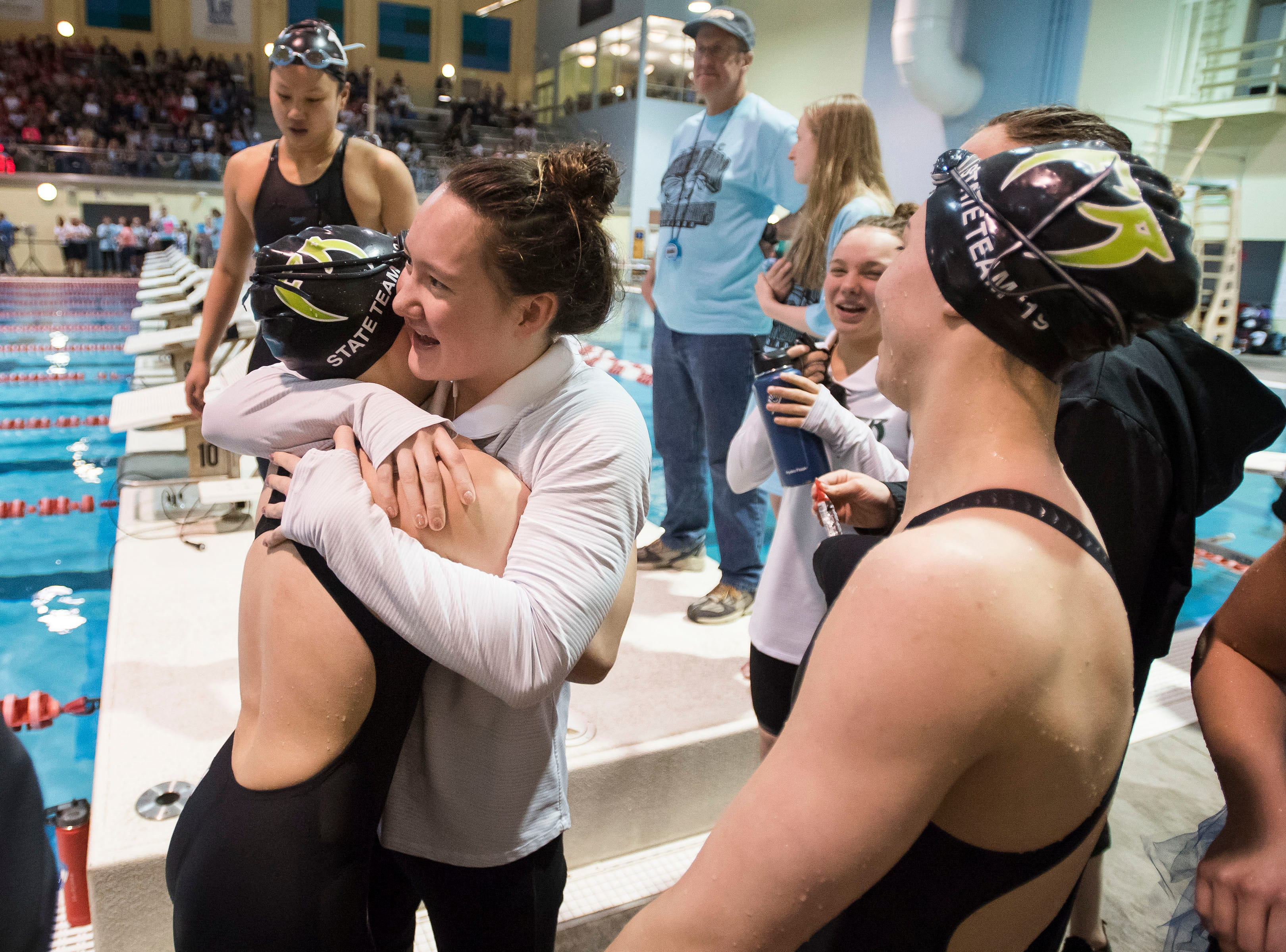 Fossil Ridge senior Coleen Gillilan hugs her younger sister, freshman Renee Gillilan, after Renee won the women's 100 yard butterfly, breaking Coleen's pool record in the race, as seen on Saturday, Feb. 9, 2019, at Veterans Memorial Aquatic Center in Thornton, Colo.
