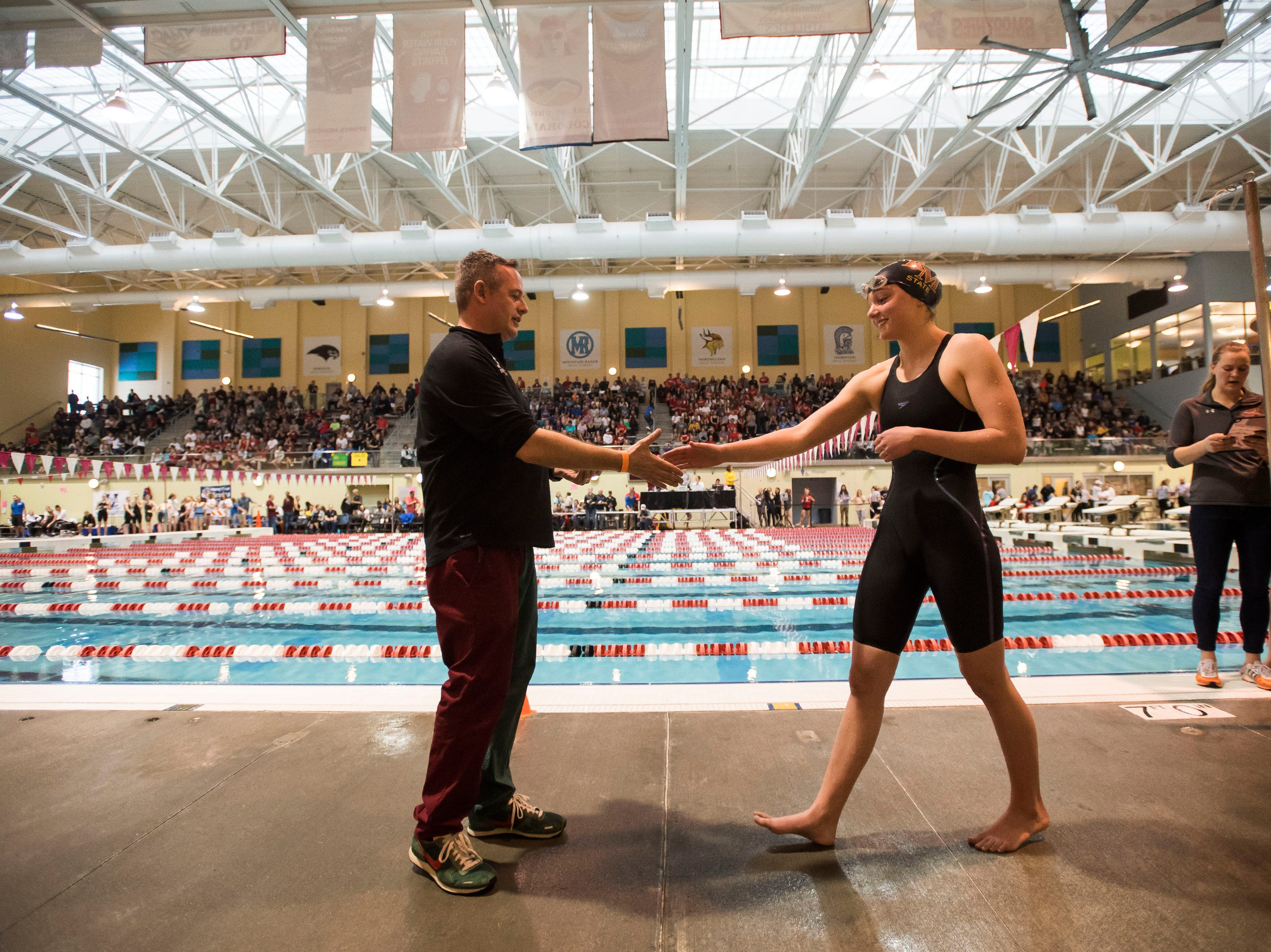 Rocky Mountain High School sophomore Meredith Smithbaker shakes hands with Scott Cohen while receiving her medal for placing second in the women's 50 yard freestyle on Saturday, Feb. 9, 2019, at Veterans Memorial Aquatic Center in Thornton, Colo.