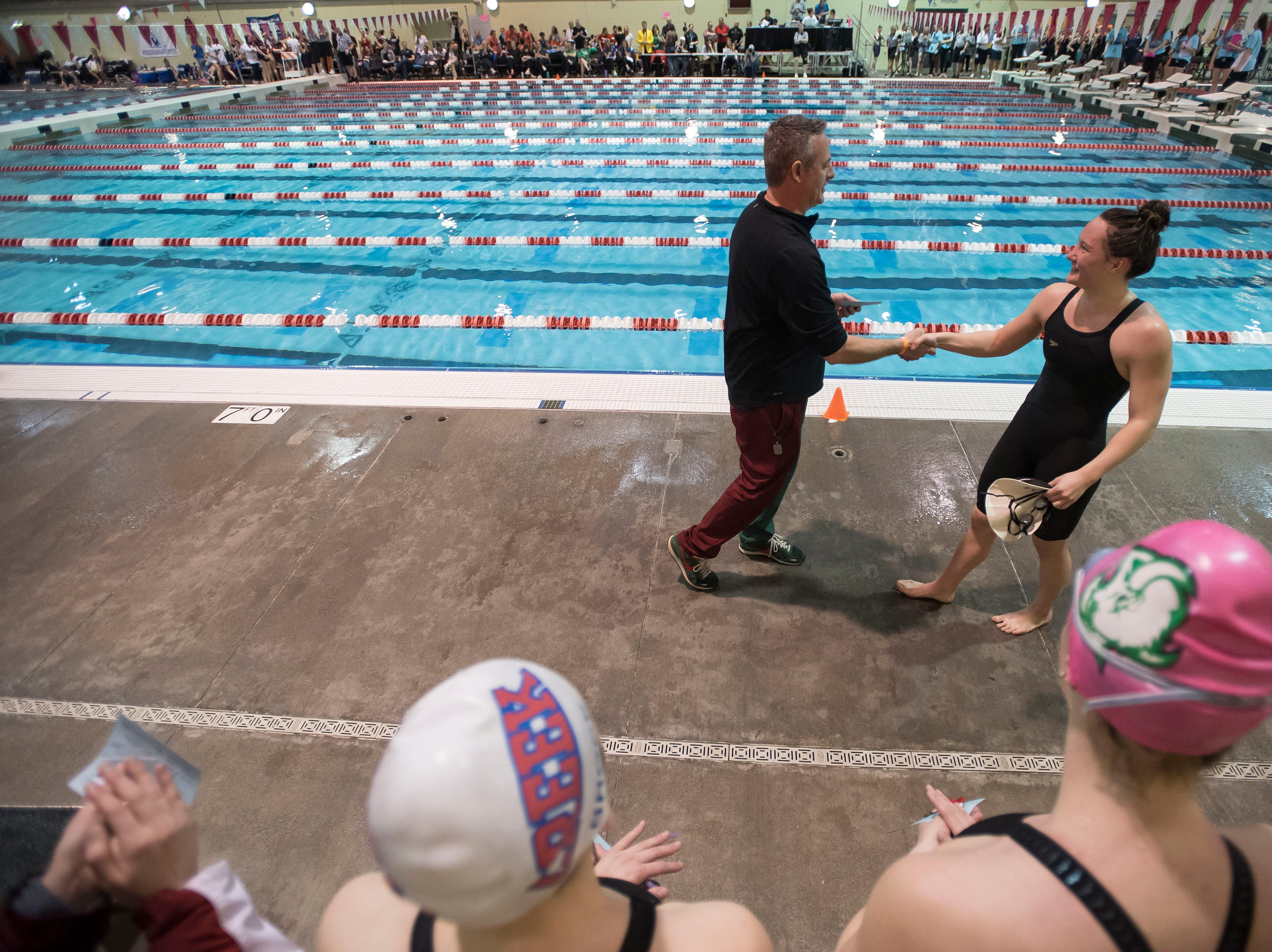 Fossil Ridge High School senior Coleen Gillilan shakes hands with Scott Cohen while receiving her medal for winning the women's 100 yard backstroke on Saturday, Feb. 9, 2019, at Veterans Memorial Aquatic Center in Thornton, Colo.