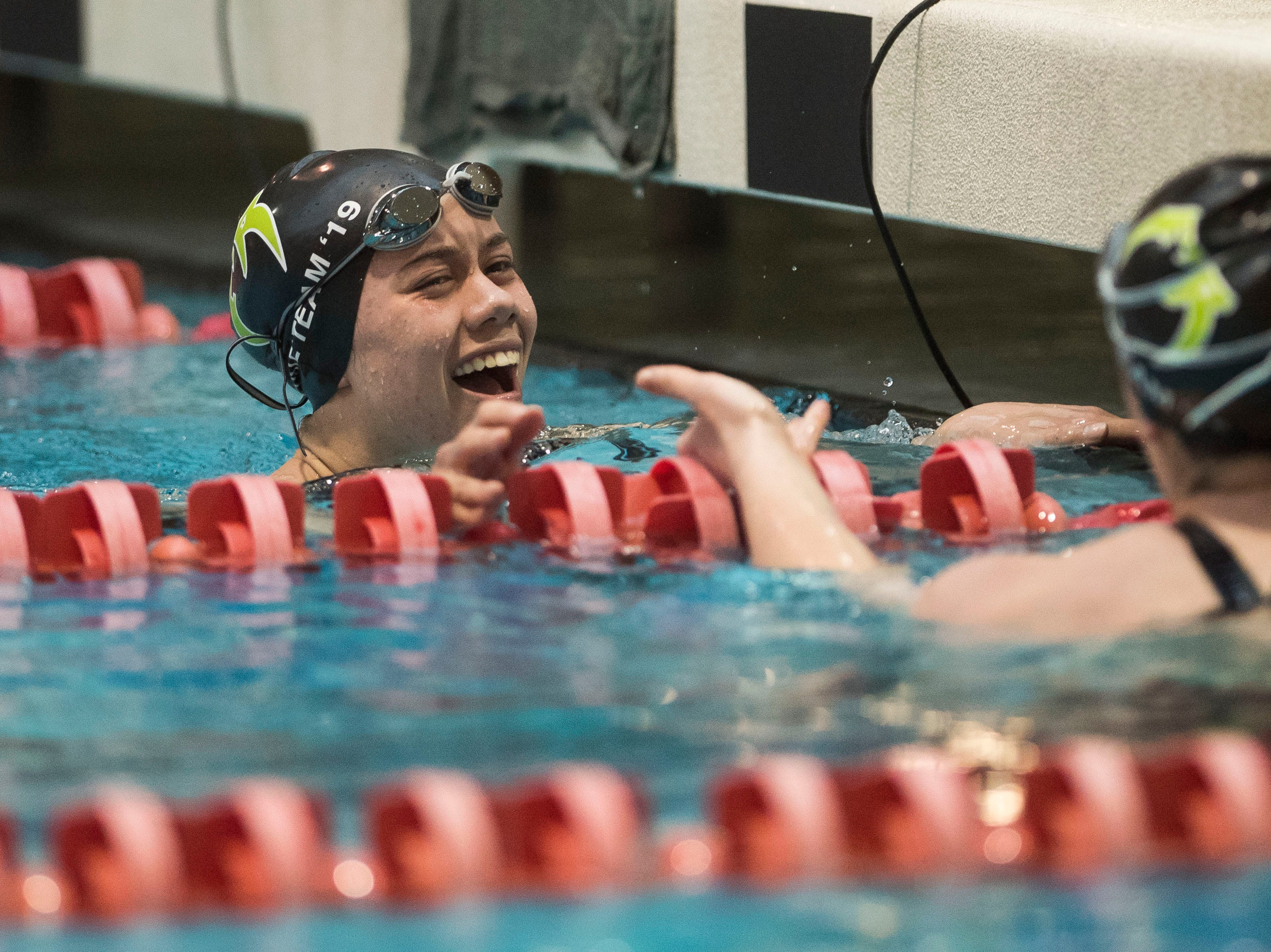 Fossil Ridge freshman Lucy Bell reaches for junior teammate Caraline Baker after winning the women's 100 yard butterfly on Saturday, Feb. 9, 2019, at Veterans Memorial Aquatic Center in Thornton, Colo.
