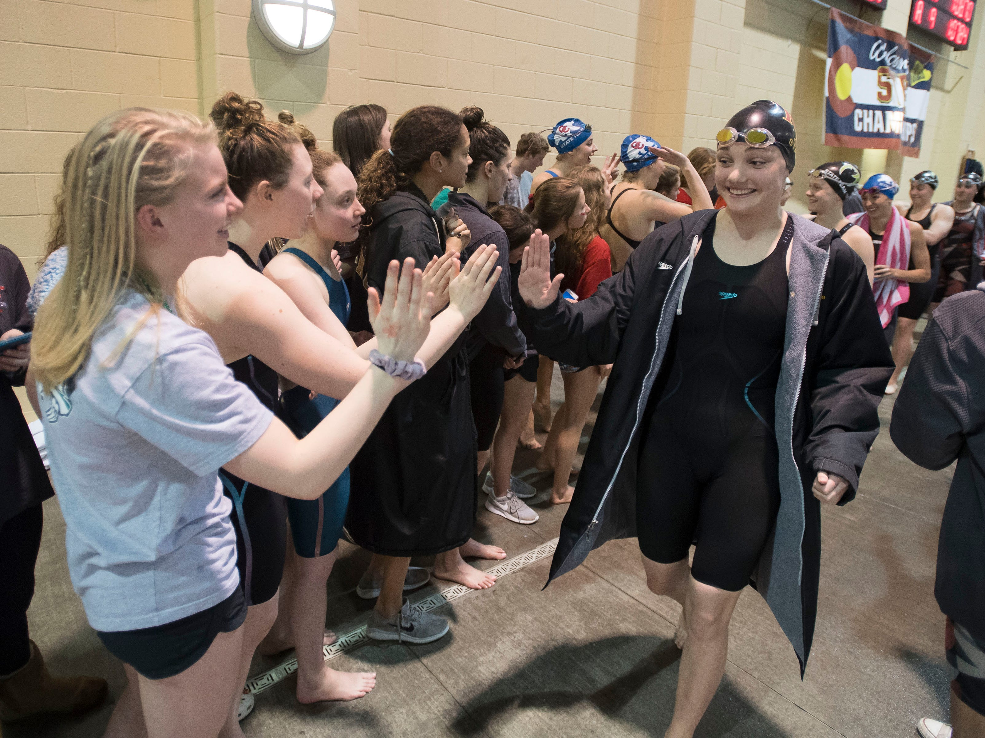 Rocky Mountain High School sophomore Meredith Smithbaker gets high-fives on her way to the starting blocks on Saturday, Feb. 9, 2019, at Veterans Memorial Aquatic Center in Thornton, Colo.