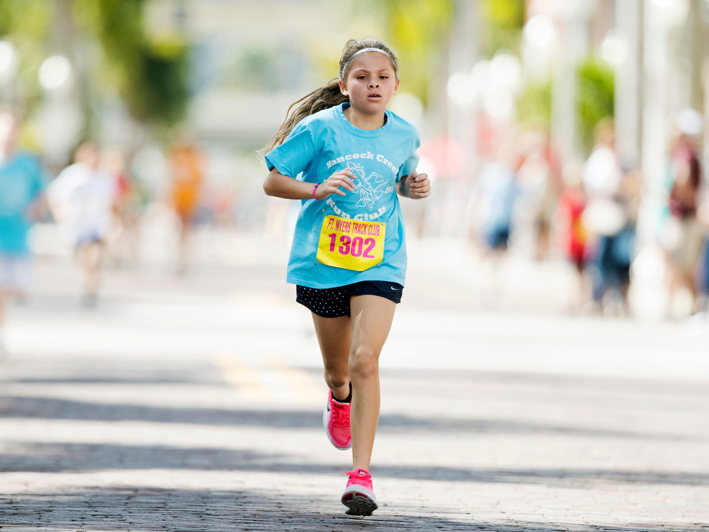 Kenlee Dominguez, 9, wins the mile race in the Edison Festival of Light Junior Fun Run on Sunday in downtown Fort Myers. Kenlee was among more than 300 kids to compete in the races.