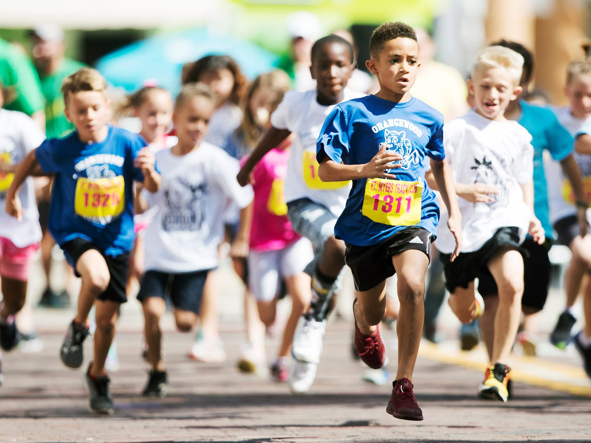 Kai Nesfield, 8, center, was among more than 300 kids to run in the Edison Festival of Light Junior Fun Run races on Sunday in downtown Fort Myers.