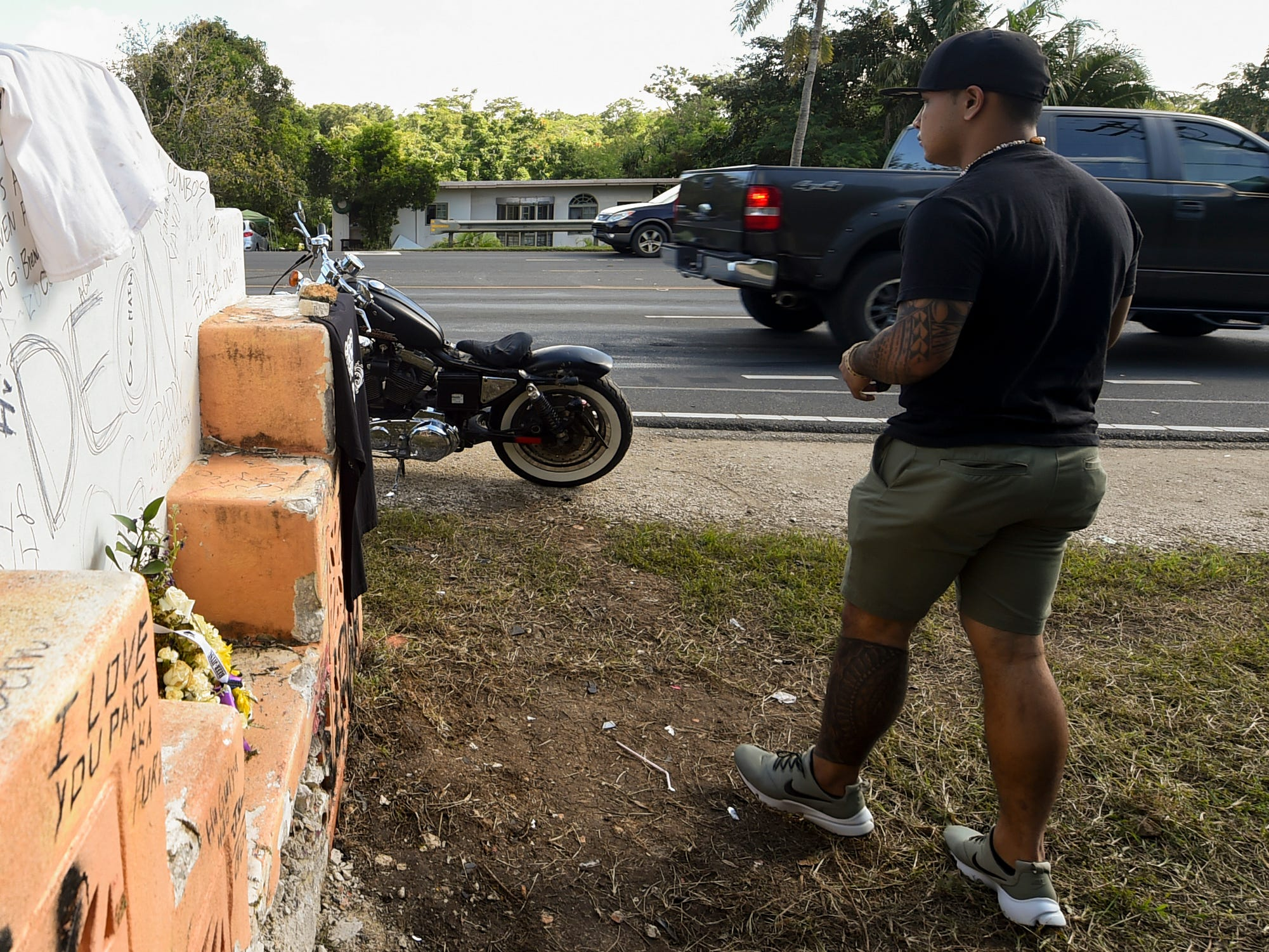 Taga Santos walks from the concrete sign at the fatal Ordot crash site of his best friend, Deon Cruz, 19, after decorating it with Cruz's favorite type of T-shirt, Feb. 10, 2019.