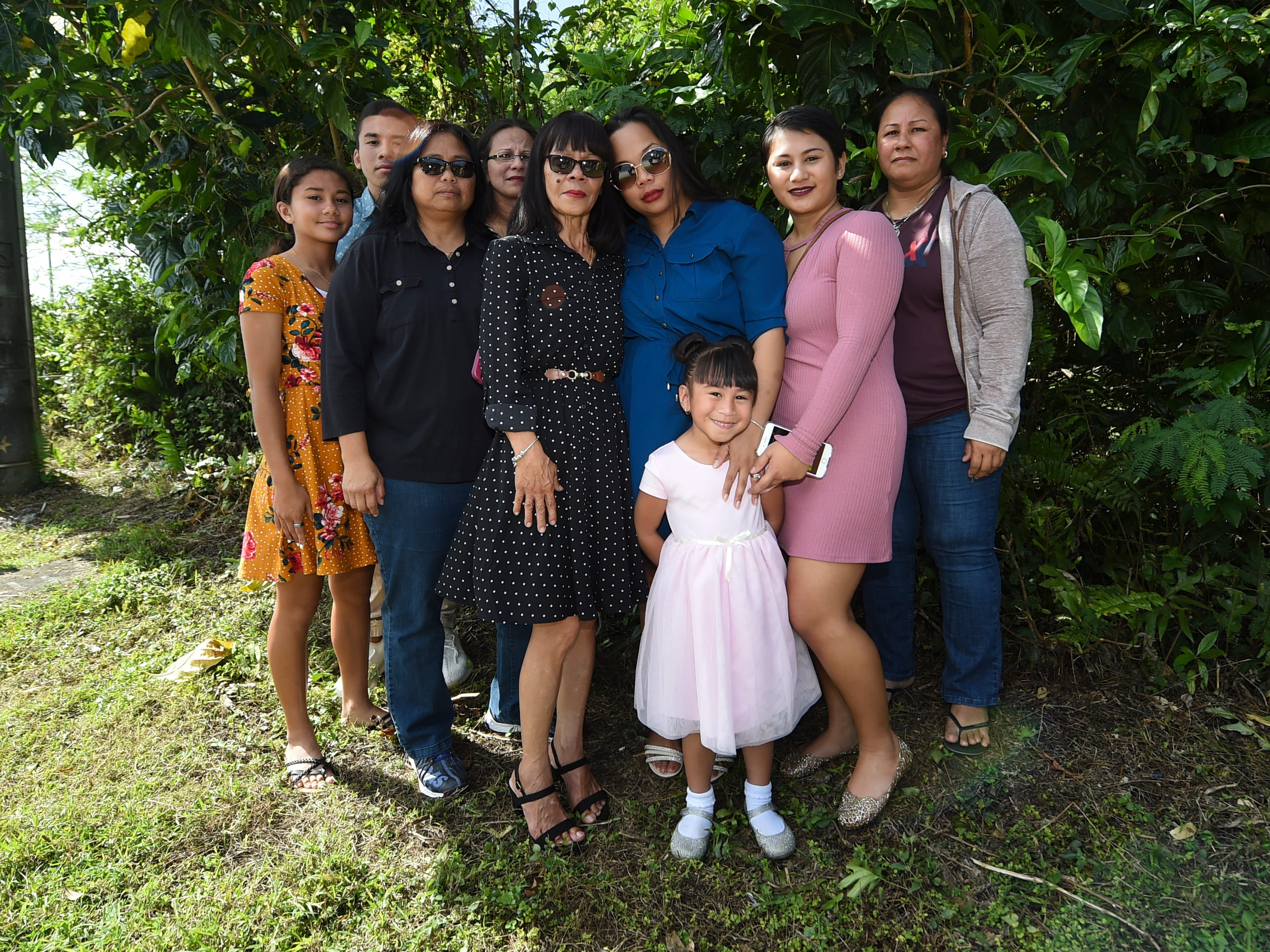 Relatives of the late Deon Cruz, 19, including his mother Charmaine Cruz, third from right, and grandmother Barbara Quidachay, center, gather for memorial photos at the Ordot crash site on Feb. 10, 2019.