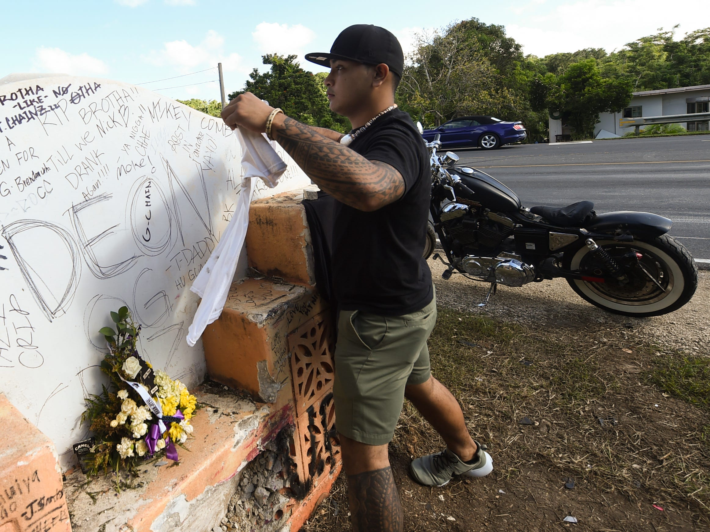 Taga Santos places a white T-shirt, a significant piece of clothing of his best friend and fatal crash victim, Deon Cruz, 19, at the concrete sign of the Ordot crash site on Feb. 10, 2019.