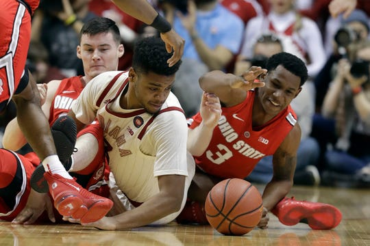 Indiana's Juwan Morgan, middle, battles for the ball against Ohio State's Kyle Young, left, and C.J. Jackson during the first half of an NCAA college basketball game, Sunday, Feb. 10, 2019, in Bloomington, Ind. (AP Photo/Darron Cummings)