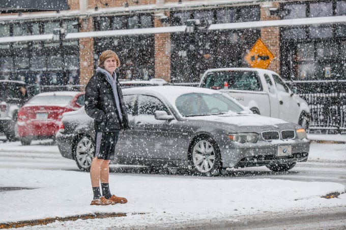 Phillip Parmelle waits to cross the street in Broad Ripple Village as now falls on Indianapolis on Sunday, Feb. 10, 2019.