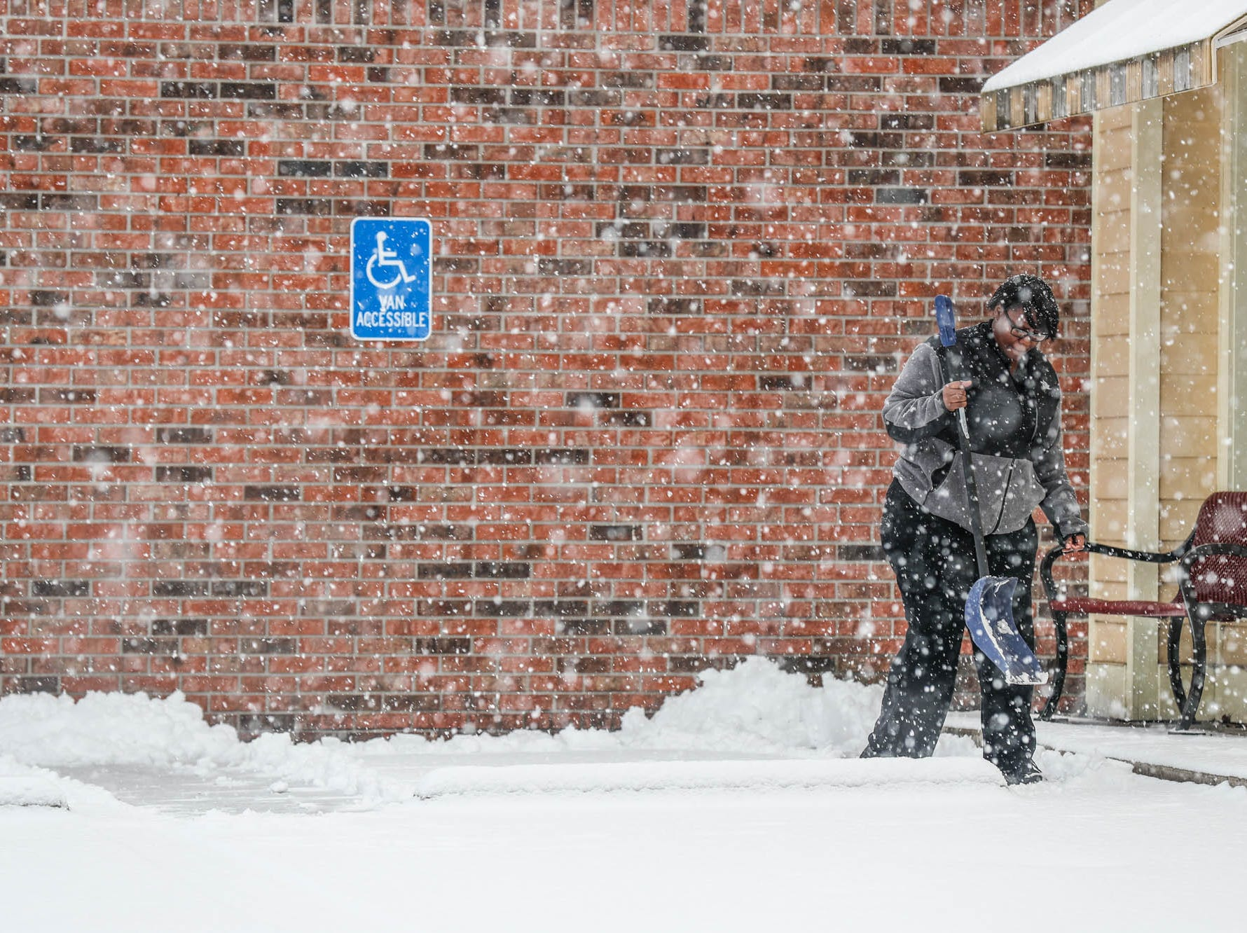 Graters Ice Cream Team Leader, Tymme Stewart-Dorris, shovels the walkway outside the ice cream parlor in  Indianapolis on Sunday, Feb. 10, 2019.