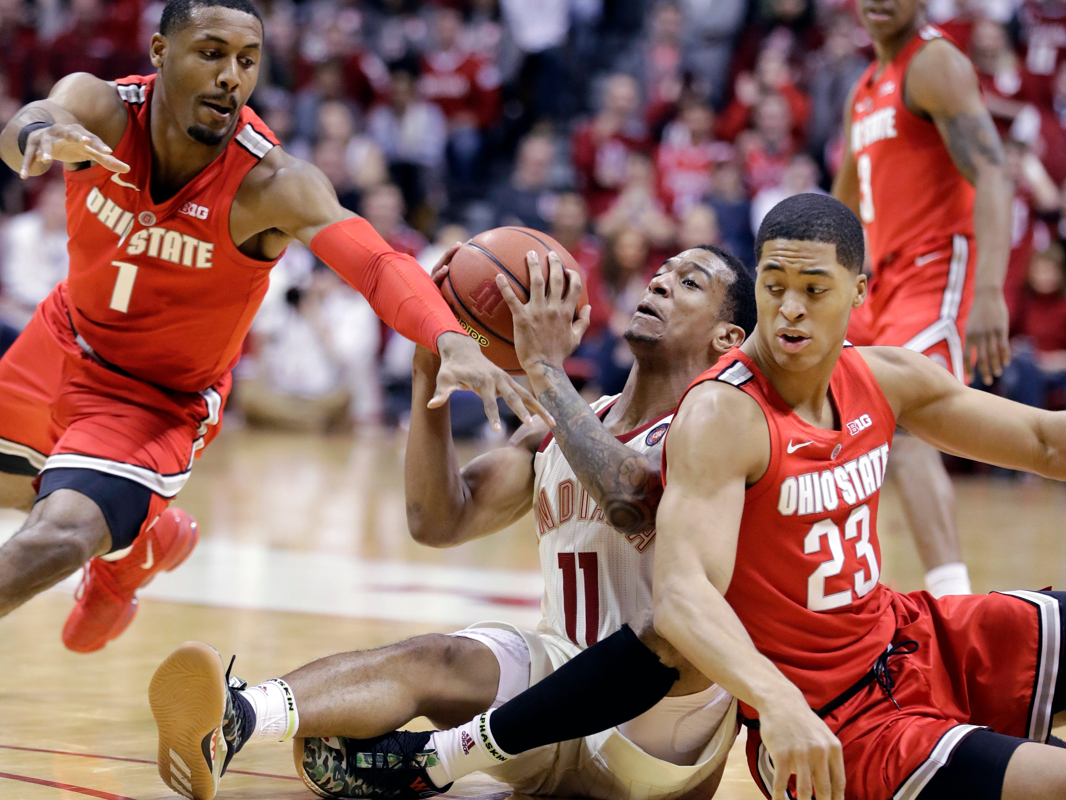 Indiana's Devonte Green (11) controls the ball against Ohio State's Luther Muhammad (1) and Jaedon LeDee (23) during the first half of an NCAA college basketball game, Sunday, Feb. 10, 2019, in Bloomington, Ind.