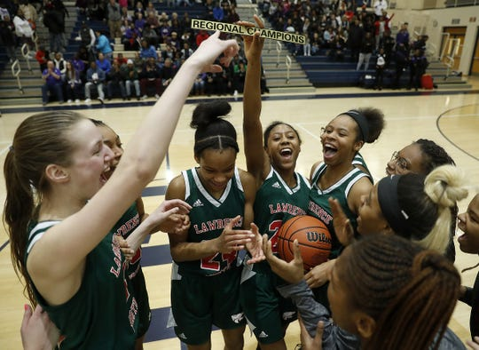 Lawrence North Wildcats Kristian Young (25) holds up the Regional Champions plaque as she celebrates her teammates following their win over the Ben Davis Giants following their IHSAA Regional Championship game at Decatur Central High School.