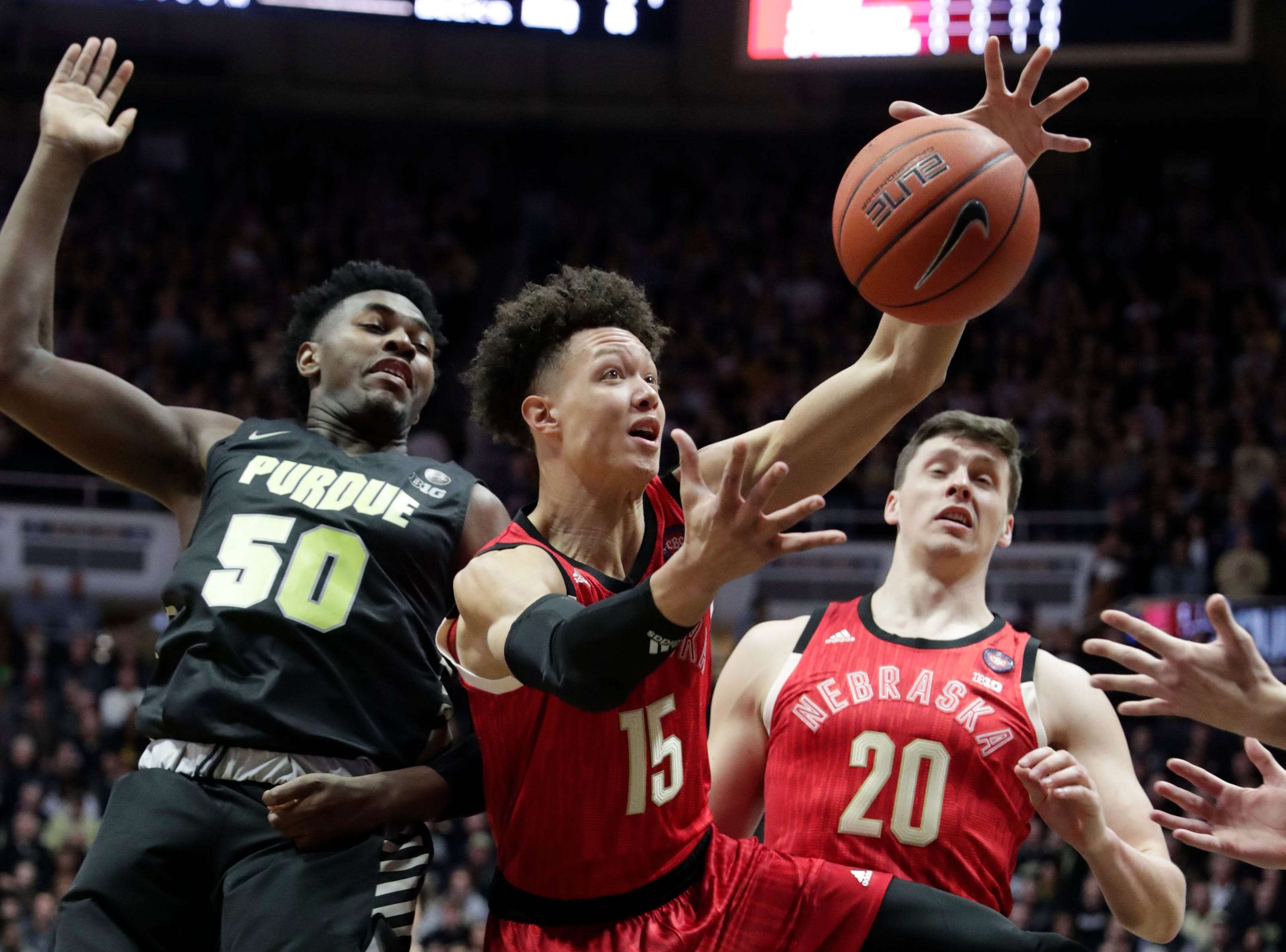 Nebraska forward Isaiah Roby (15) grabs a rebound in front of Purdue forward Trevion Williams (50) and Nebraska forward Tanner Borchardt (20) during the first half of an NCAA college basketball game in West Lafayette, Ind.