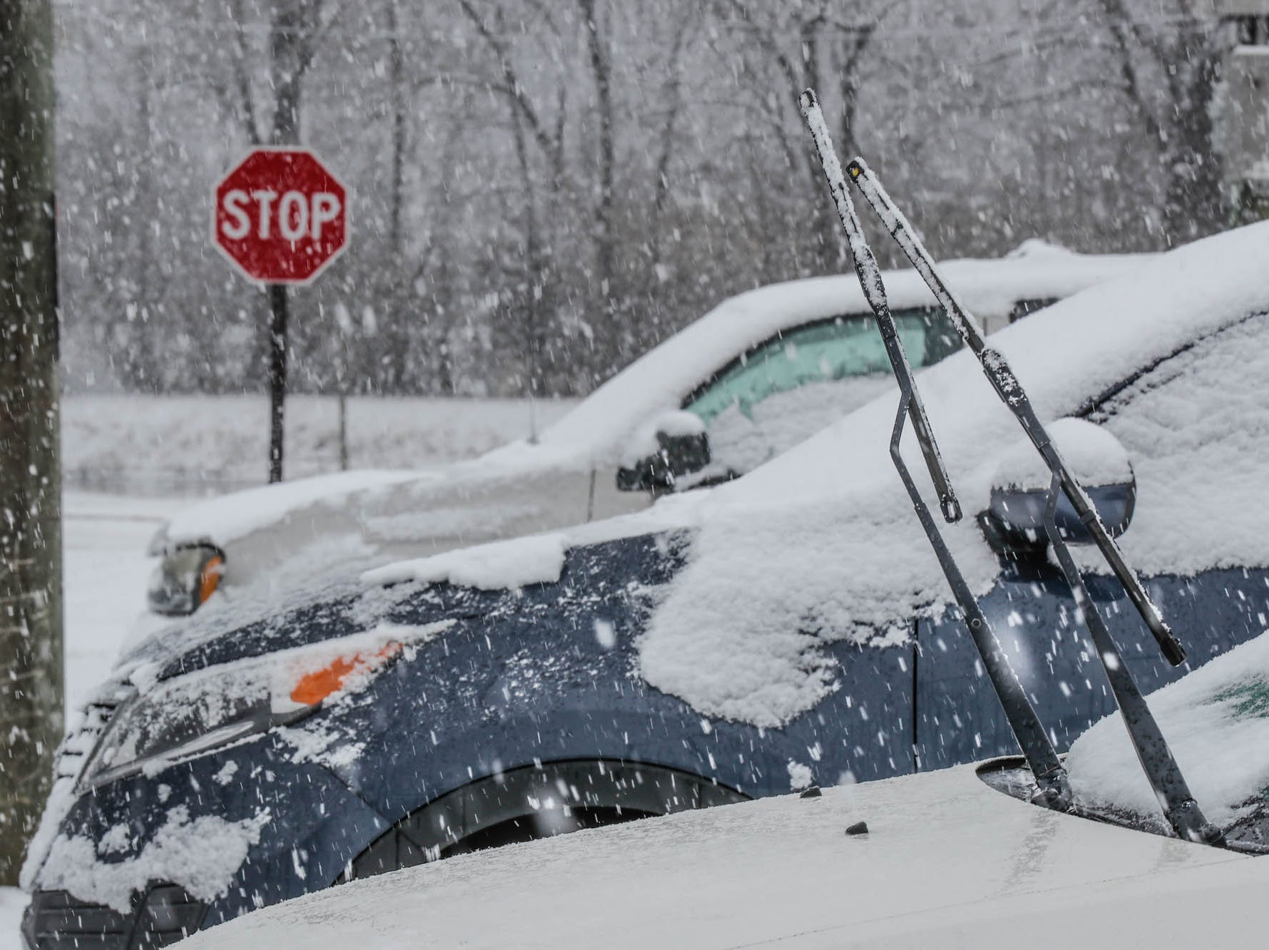 Windshield wipers are pulled up to avoid freezing as now falls in Indianapolis on Sunday, Feb. 10, 2019.