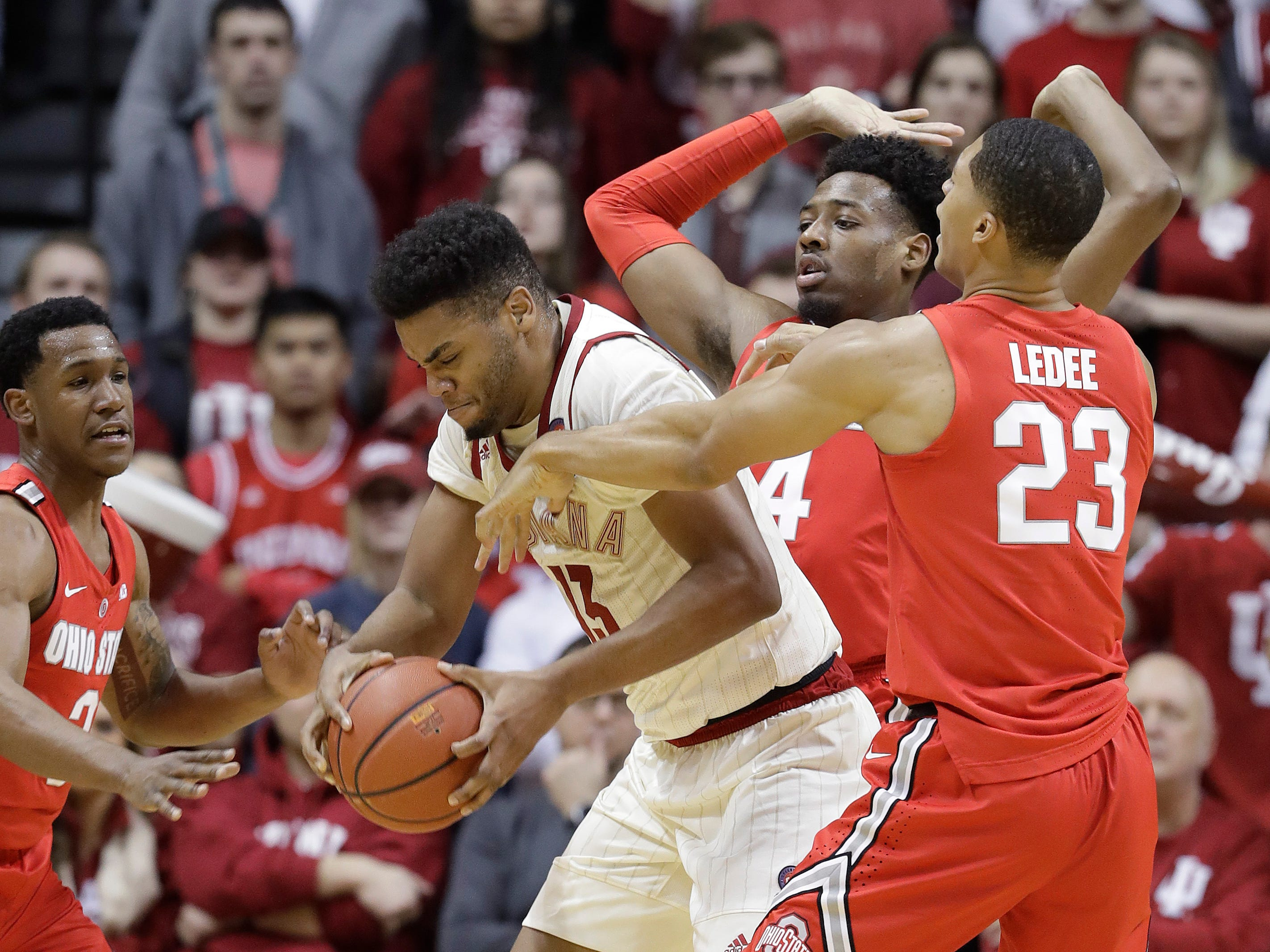 Indiana's Juwan Morgan (13) is defended by Ohio State's C.J. Jackson (3), Andre Wesson (24) and Jaedon LeDee (23) during the first half of an NCAA college basketball game, Sunday, Feb. 10, 2019, in Bloomington, Ind. (AP Photo/Darron Cummings)
