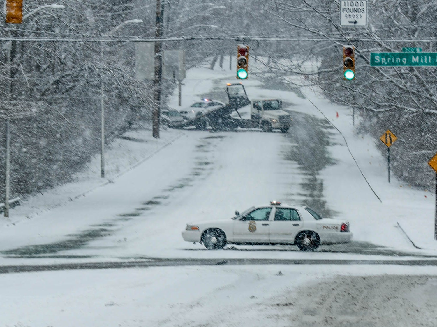 Police block the Kessler Blvd. W. Dr. hill after  a car slid off the road as now fell on Indianapolis on Sunday, Feb. 10, 2019.
