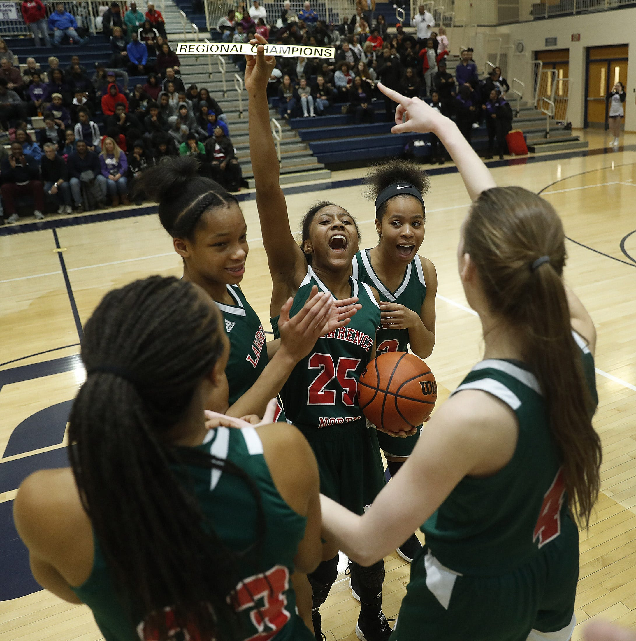 Lawrence North Wildcats Kristian Young (25) holds up the Regional Champions plaque as she celebrates her teammates following their win over the Ben Davis Giants following their IHSAA Regional Championship game at Decatur Central High School on Friday, Feb. 8, 2019. The Lawrence North Wildcats defeated the Ben Davis Giants  60-46.