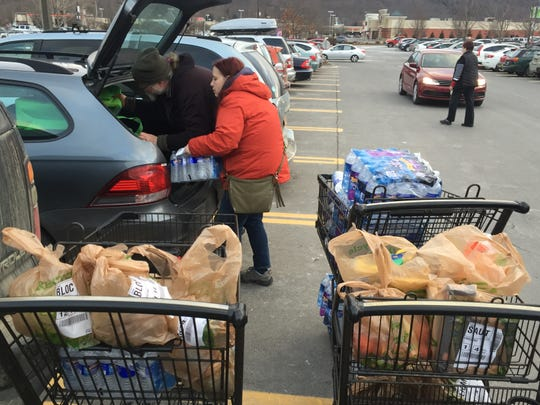 Tracy and Joe Catlin, both Instacart couriers in Ithaca, load their car with groceries.