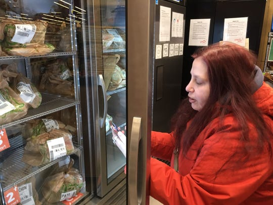 Tracy Catlin, of Ithaca, scans a delivery-only bag of groceries for Instacart.