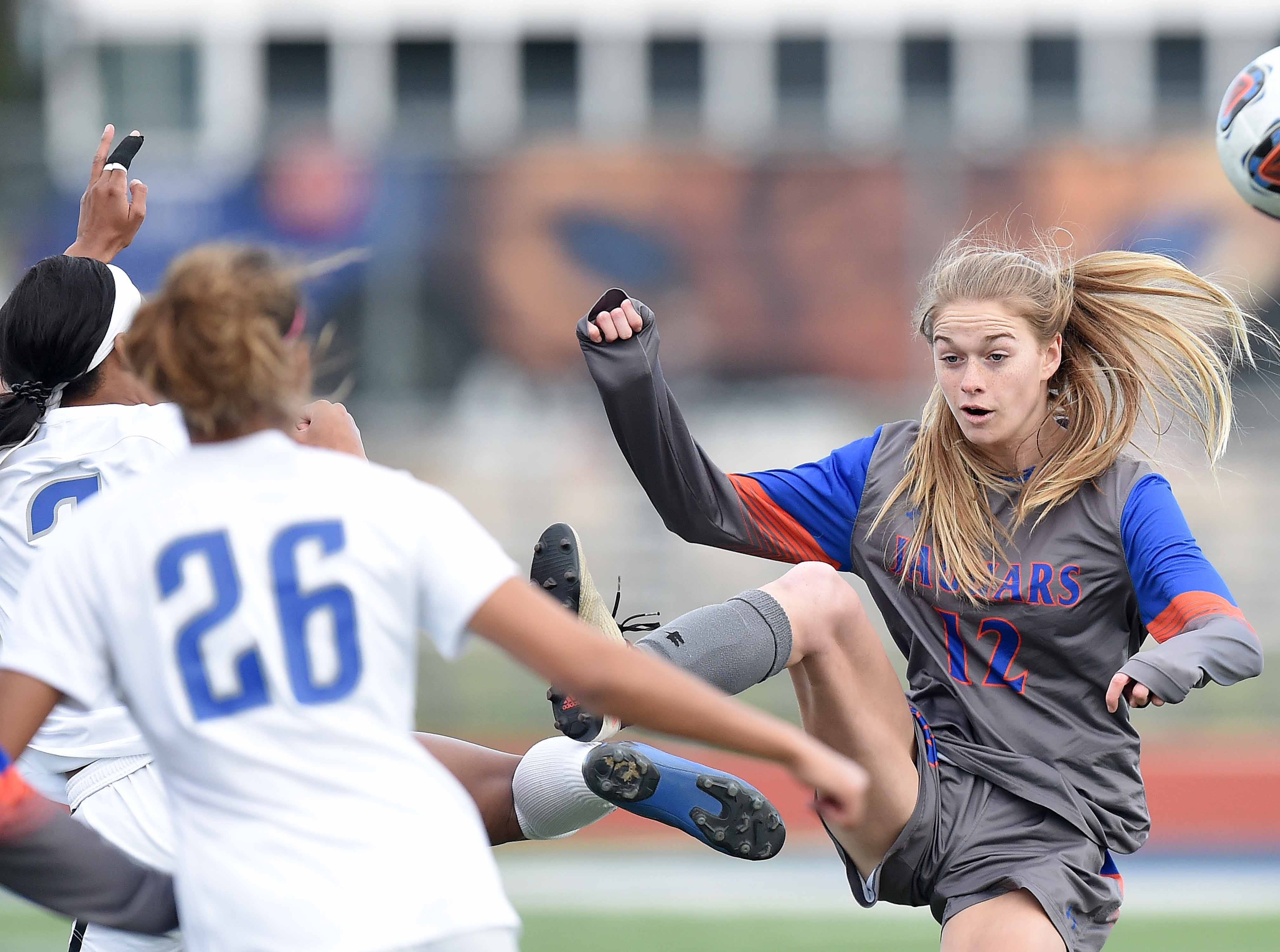 Madison Central's Savannah Turner (12) competes for a loose ball with two Ocean Springs Lady Greyhounds in the Class 6A state championship in the MHSAA BlueCross Blue Shield of Mississippi Soccer Classic on Saturday, February 9, 2019, at Ridgeland High School in Ridgeland, Miss.