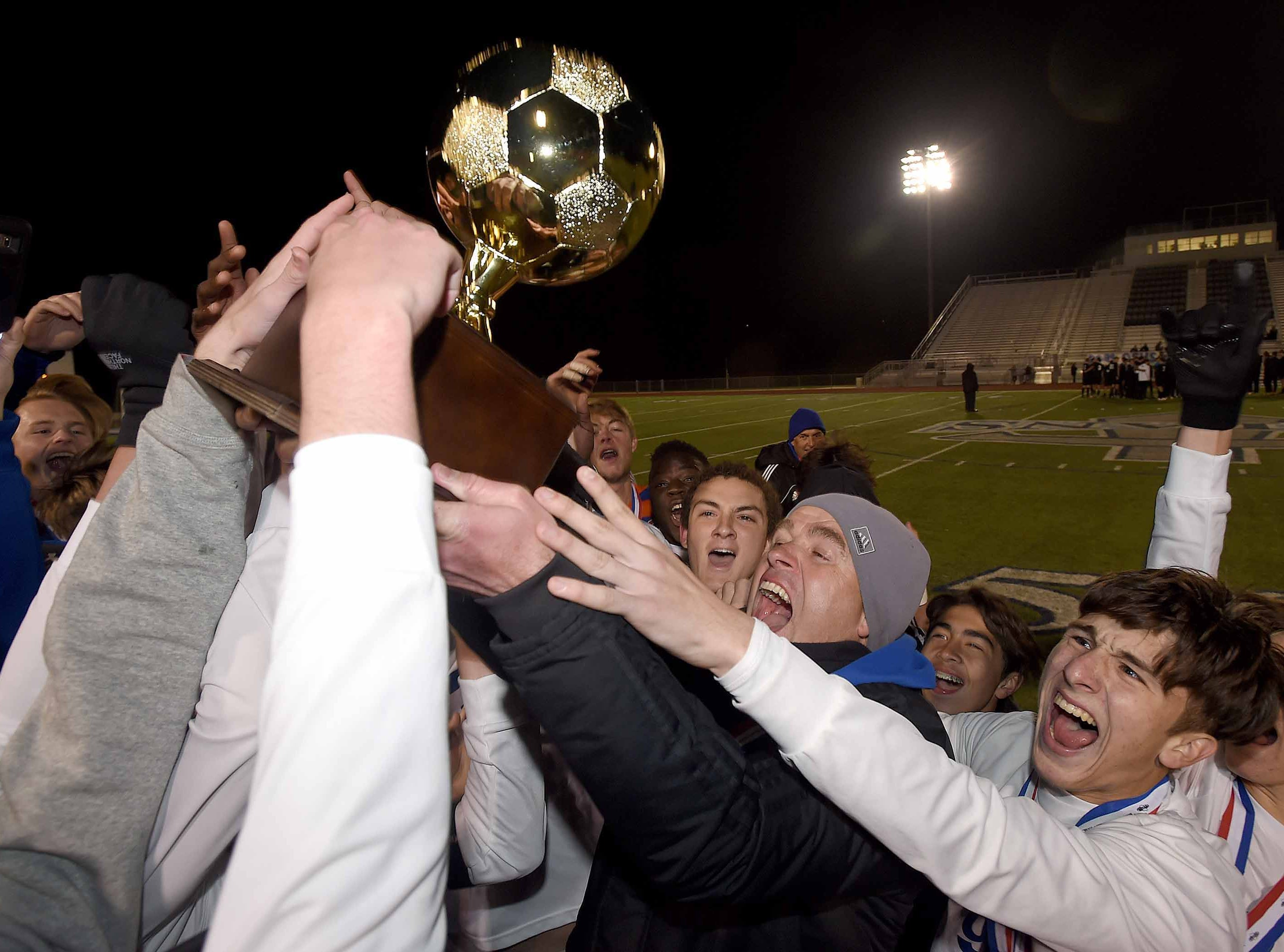 The Gulfport Admirals and head coach Henrik Madsen celebrate with the Class 6A state championship trophy after defending their 2018 state title beating Northwest Rankin 2-1 in the MHSAA BlueCross Blue Shield of Mississippi Soccer Classic on Saturday, February 9, 2019, at Ridgeland High School in Ridgeland, Miss.