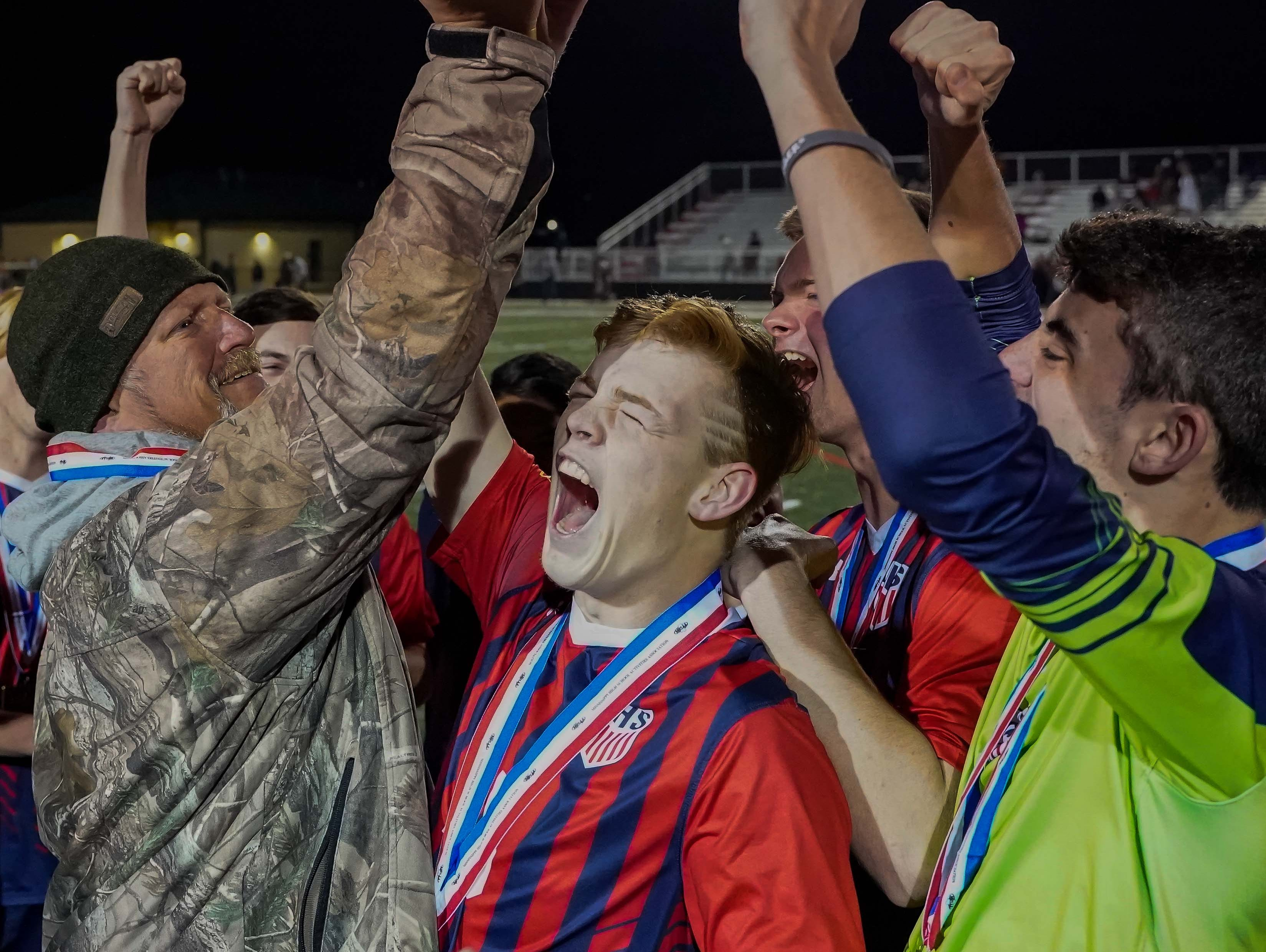 Lewisburg coach Harl Roehm hoists the trophy with his players following the Patriots 2-1 win against Long Beach during the MHSAA 5A Boys Soccer Championships held at Brandon High School in Brandon, MS, Saturday February 9, 2019.(Bob Smith-For The Clarion Ledger)