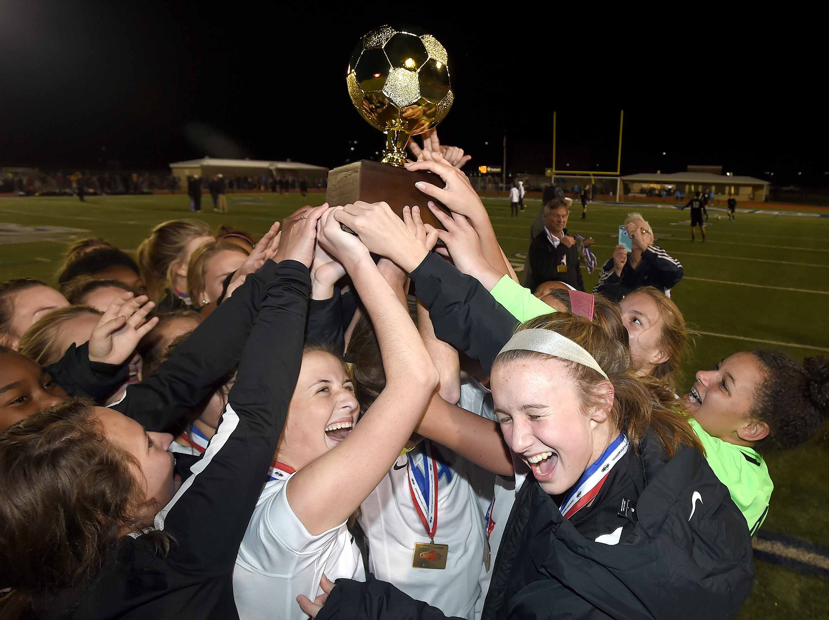 The Ocean Springs Lady Greyhounds celebrate with the Class 6A state championship trophy after beating Madison Central 1-0 on penalty kicks after overtime periods in the MHSAA BlueCross Blue Shield of Mississippi Soccer Classic on Saturday, February 9, 2019, at Ridgeland High School in Ridgeland, Miss.