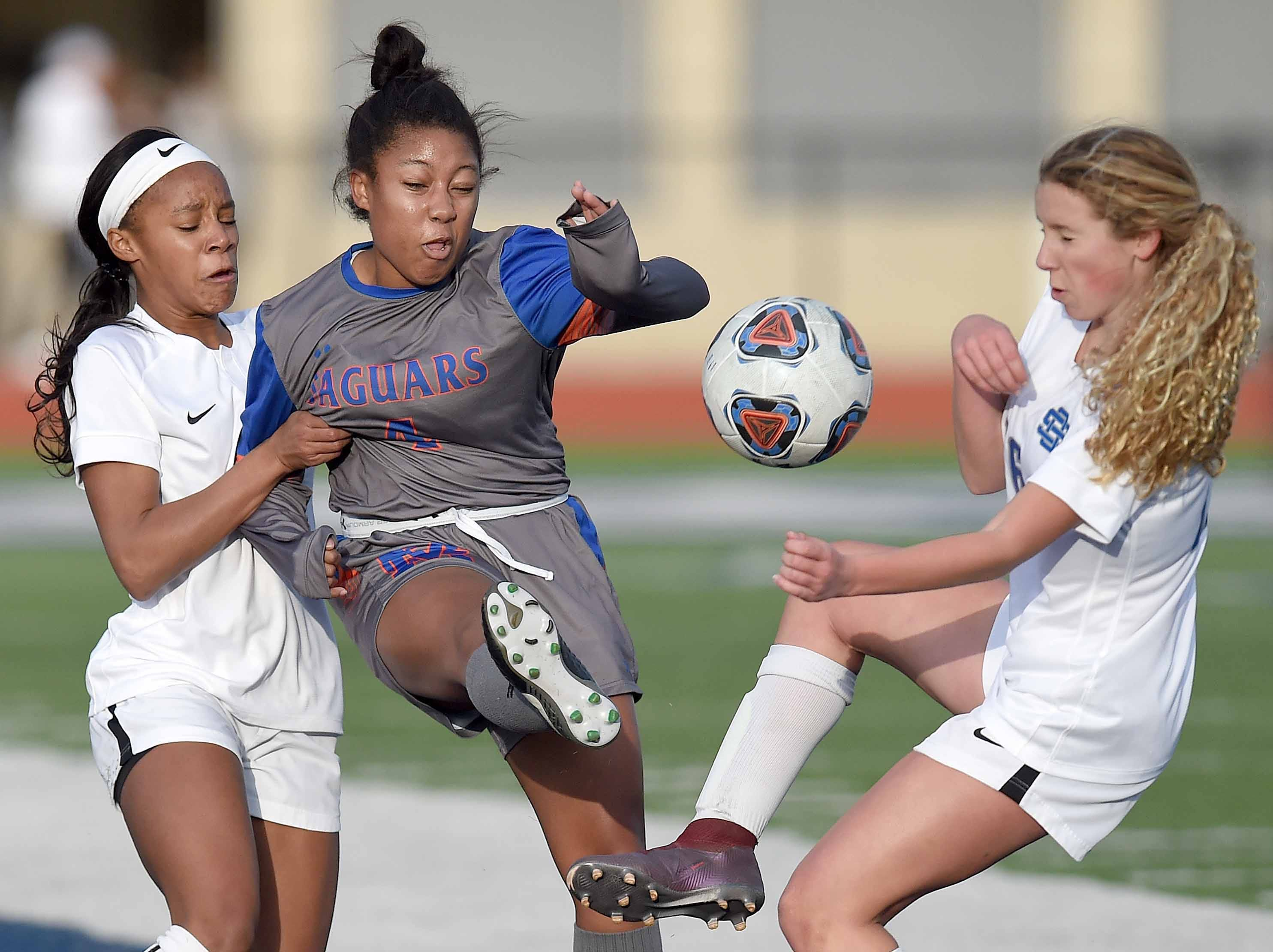 Madison Central's Elaysha Travis (4) clears the ball between two Ocean Springs Lady Greyhounds in the Class 6A state championship in the MHSAA BlueCross Blue Shield of Mississippi Soccer Classic on Saturday, February 9, 2019, at Ridgeland High School in Ridgeland, Miss.