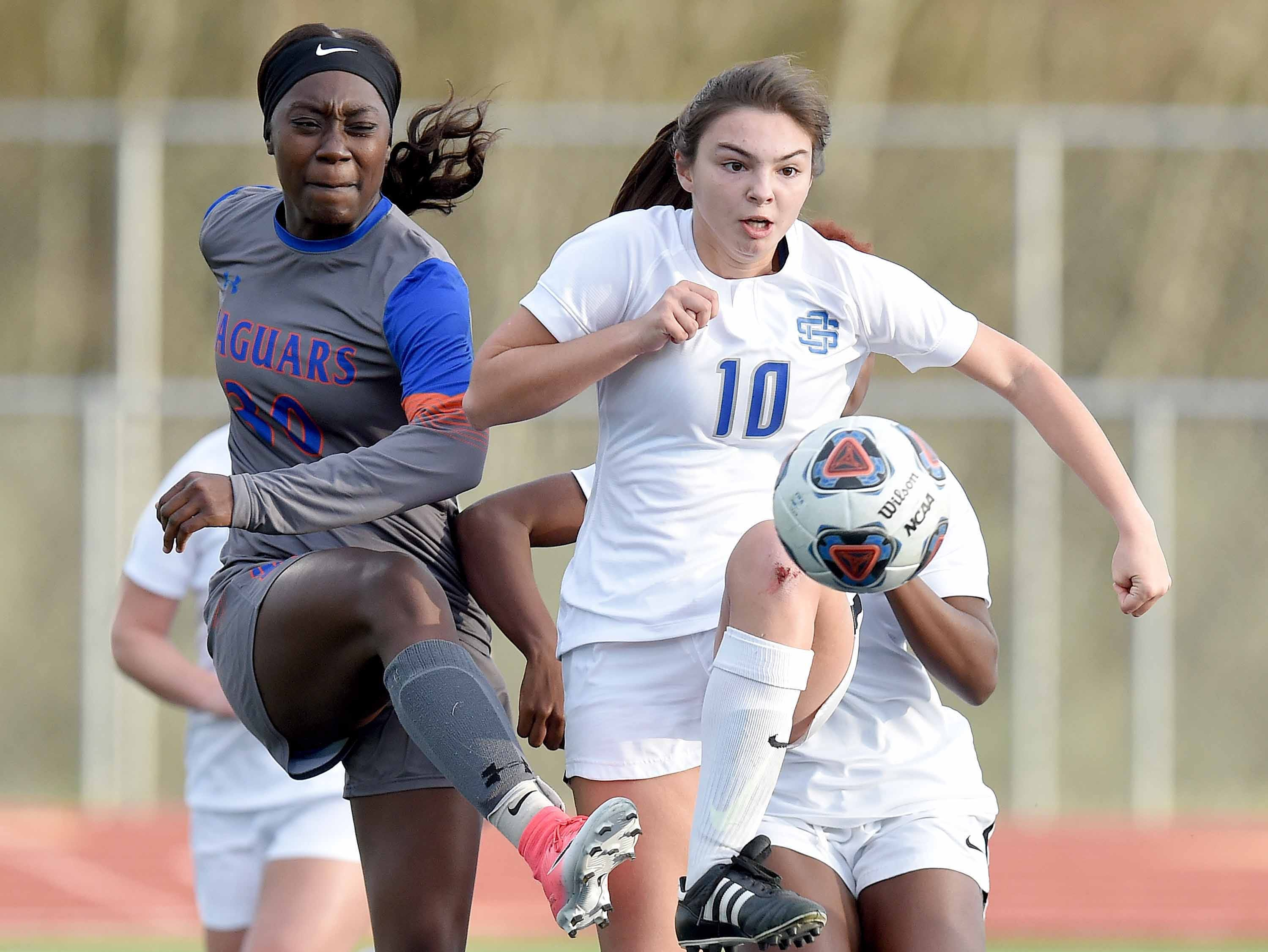 Madison Central's Cariel Ellis (30) and Ocean Springs' Jackie Dilorenzo (10) fight for a loose ball in the Class 6A state championship in the MHSAA BlueCross Blue Shield of Mississippi Soccer Classic on Saturday, February 9, 2019, at Ridgeland High School in Ridgeland, Miss.