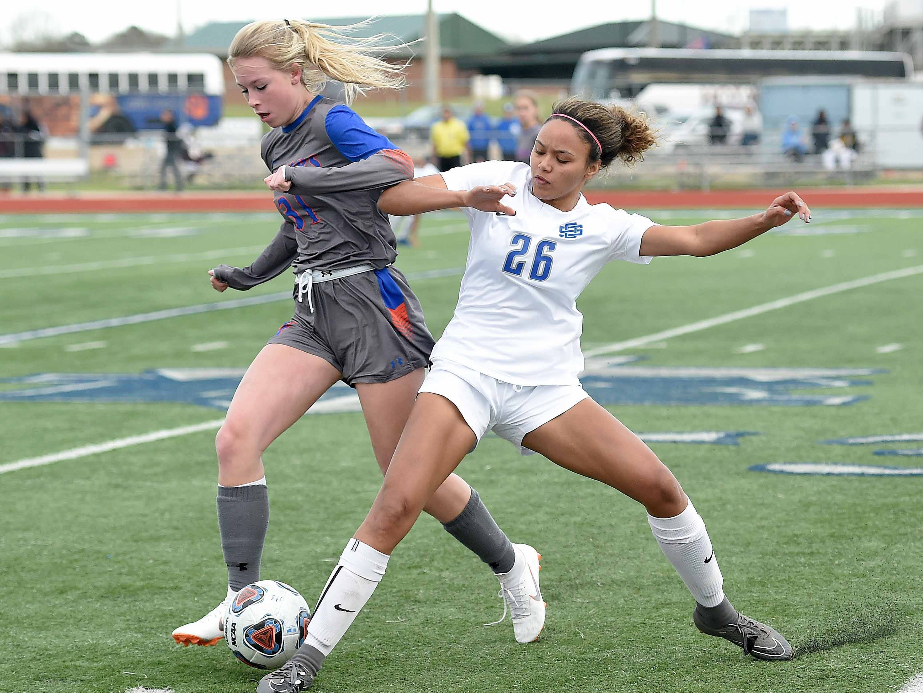 Madison Central's Anna Christia Farmer (31) and Ocean Springs' Ameris Taylor (26) compete for a ball near the sidelines in the Class 6A state championship in the MHSAA BlueCross Blue Shield of Mississippi Soccer Classic on Saturday, February 9, 2019, at Ridgeland High School in Ridgeland, Miss.