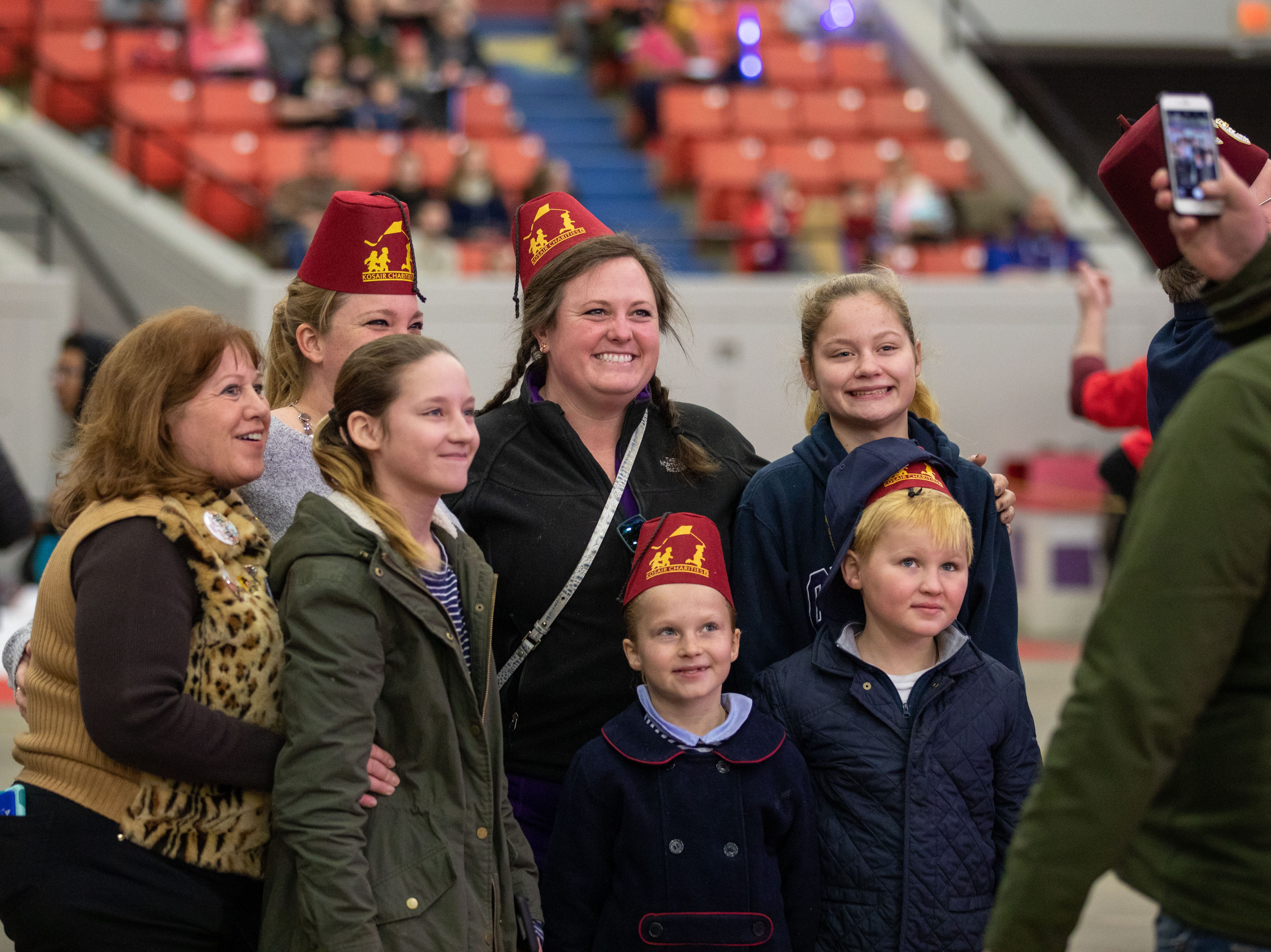 Wearing grins and Kosair Shriner hats, a group poses for a photo in Broadbent Arena before the circus begins, Saturday, Feb. 9, 2019 in Louisville Ky.