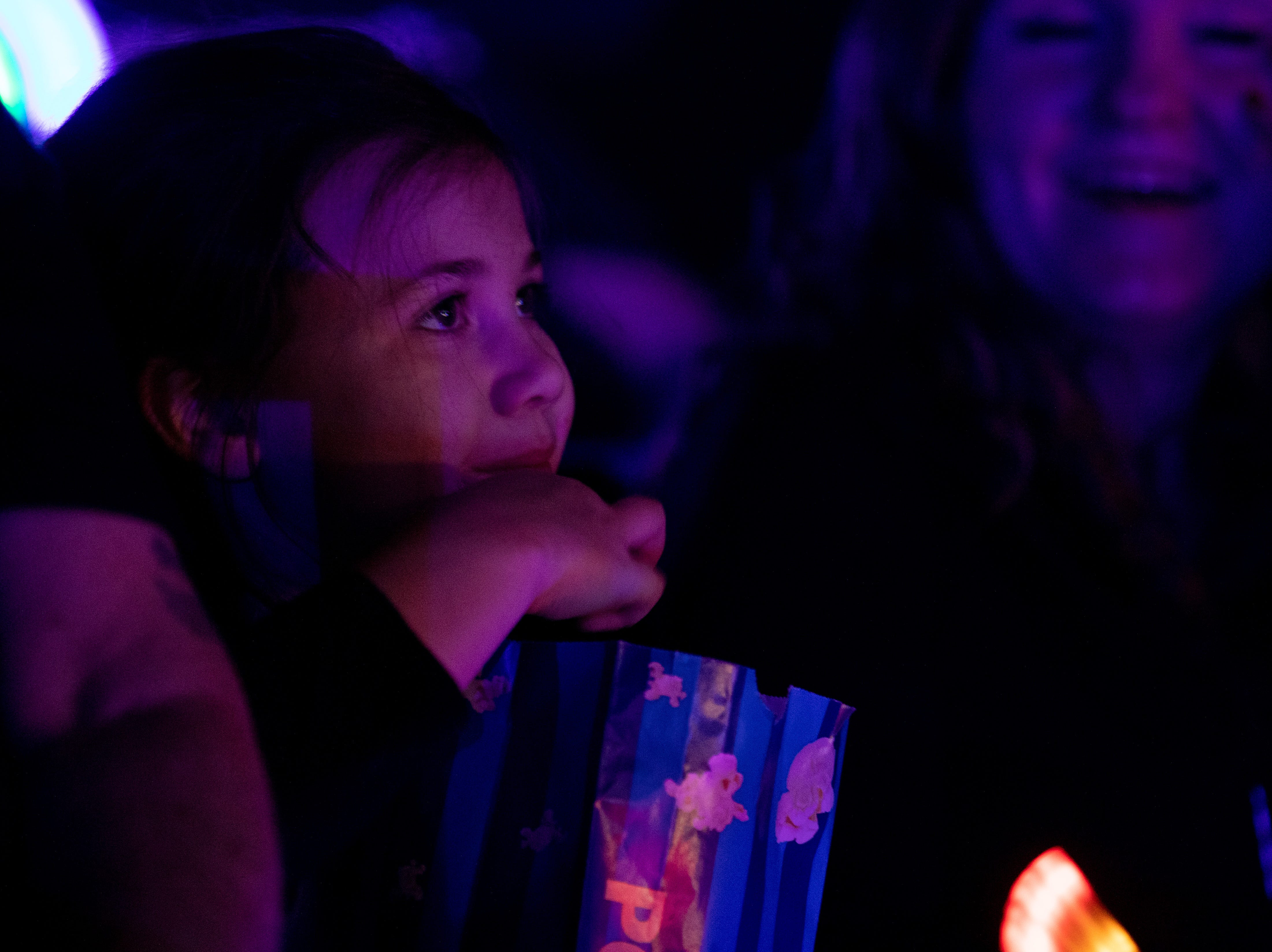 A young spectator watches the circus while snacking on popcorn, Saturday, Feb. 9, 2019 in Louisville Ky.